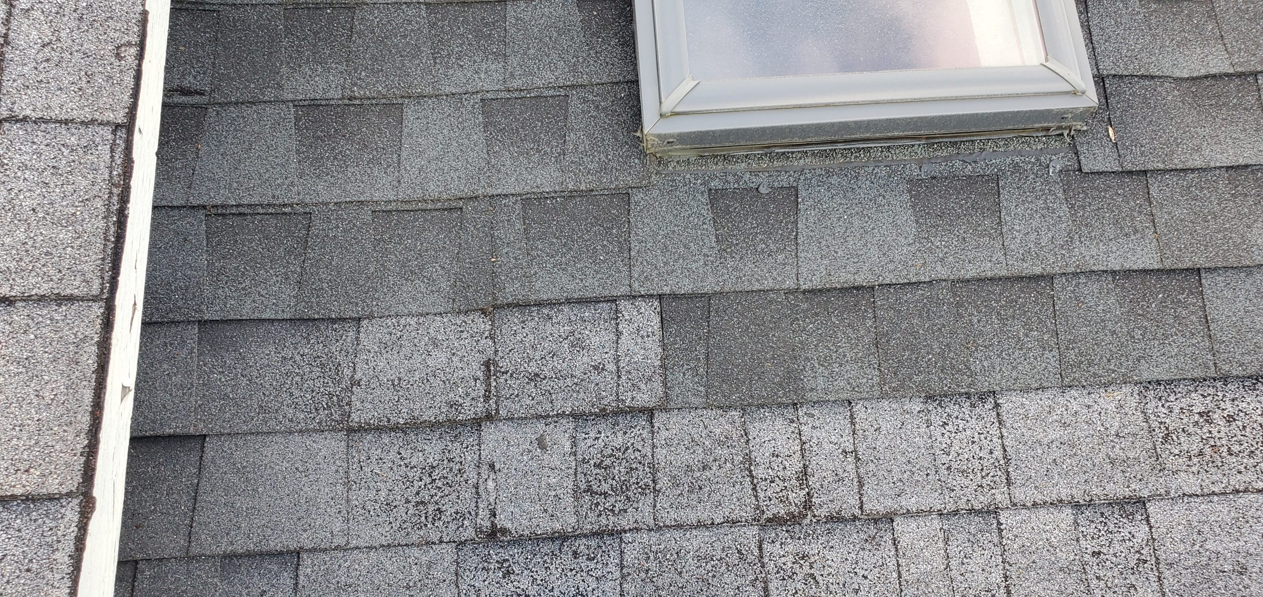 this is a picture showing new shingles next to old shingles where a skylight has been repaired in sevierville tn