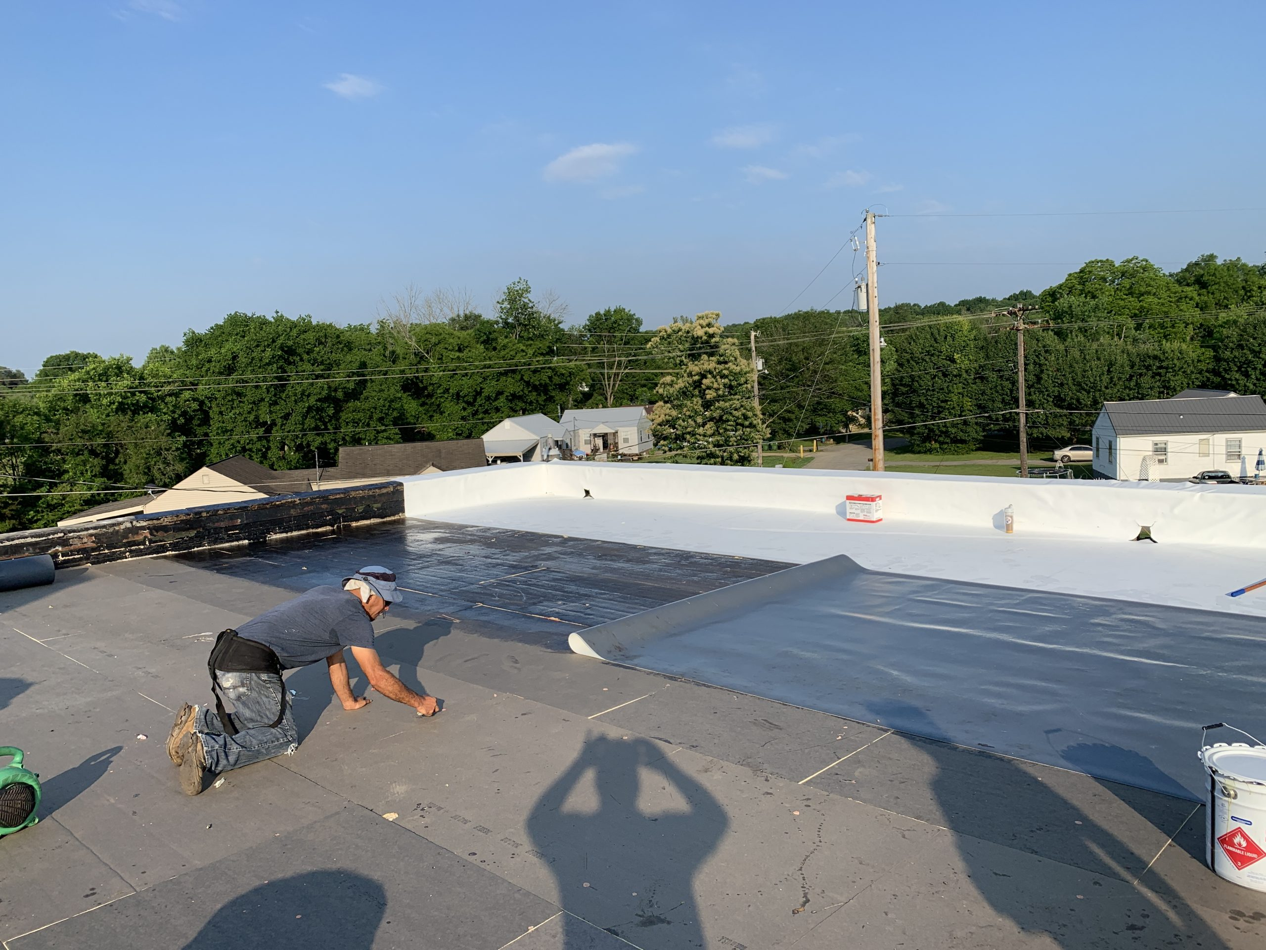 worker working on commercial roofing system that has tapered iso boards