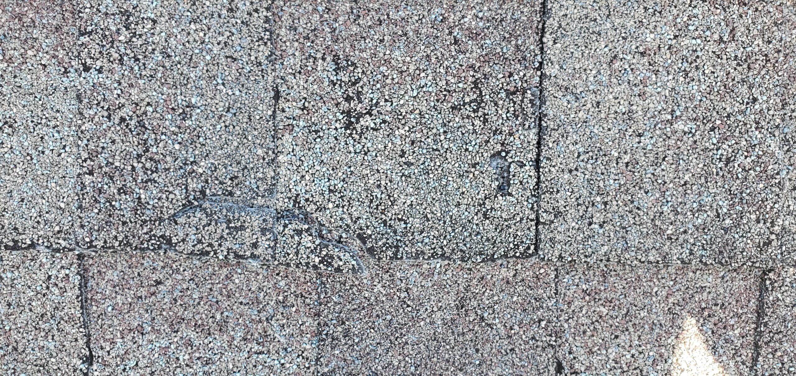 this is a picture showing weather and cracking dimensional singles that are weathered wood in color