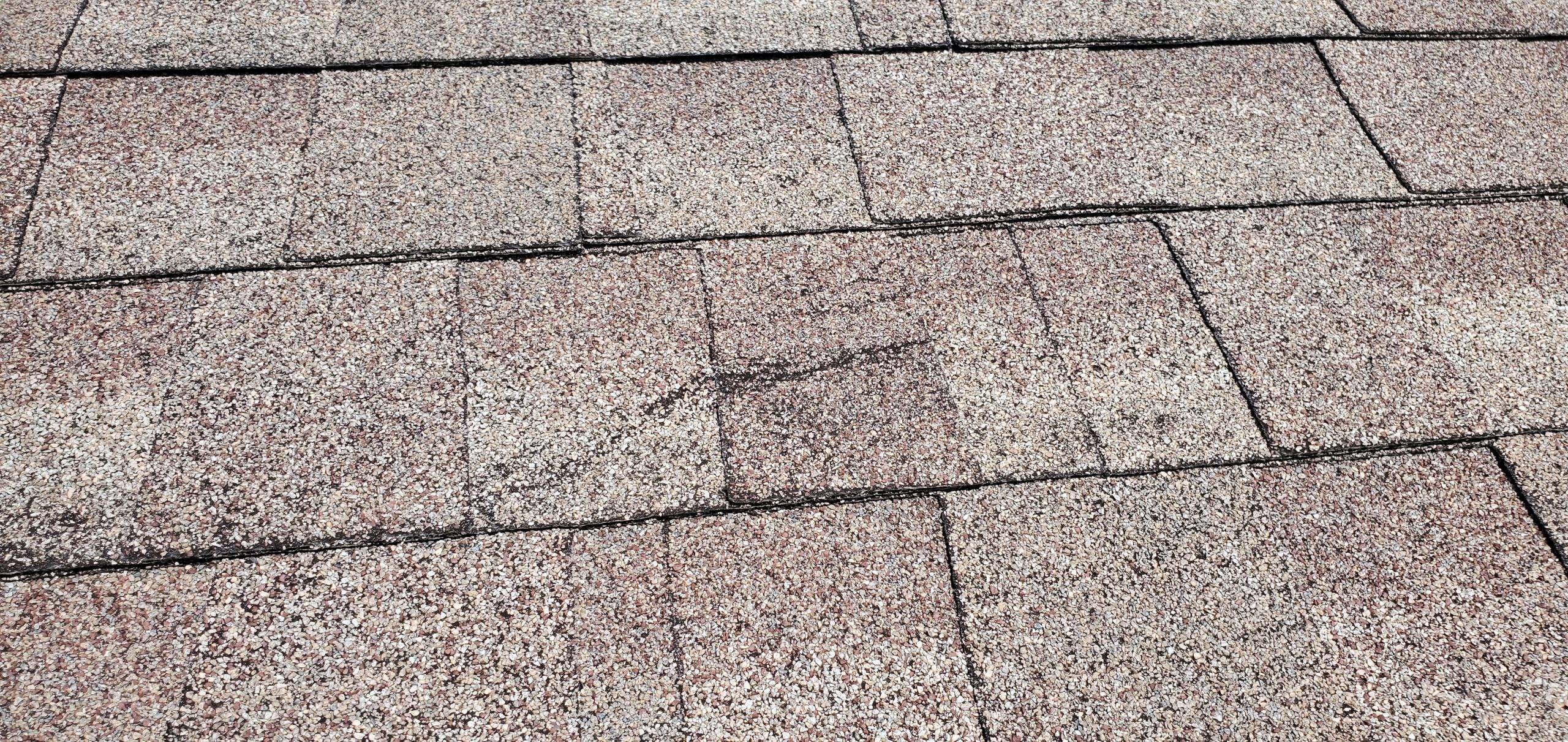 this is a picture of a big crack in roof shingles that can cause roof leaks in sevierville tn