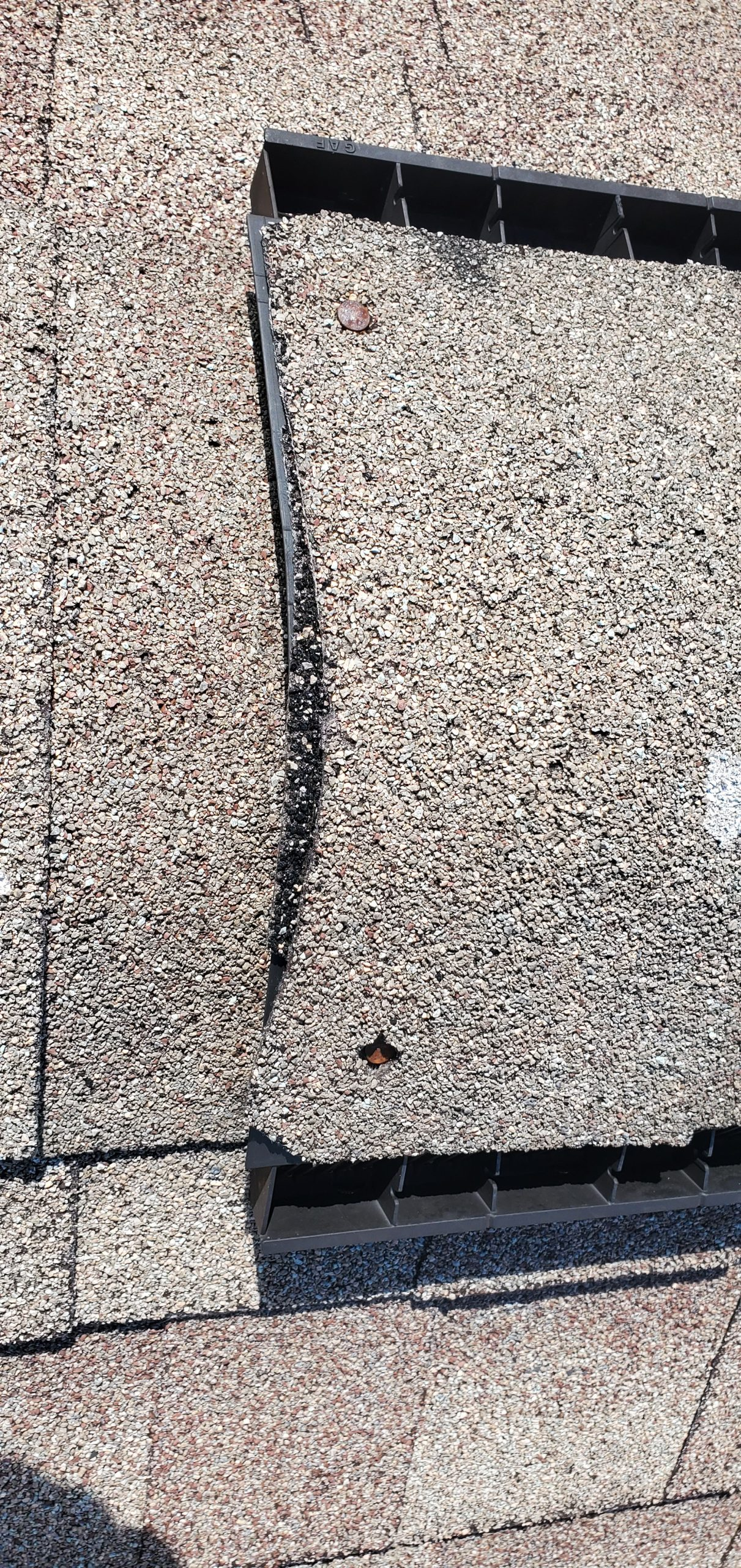 this is a picture of an exposed nail that is on a ridge vent of a roof
