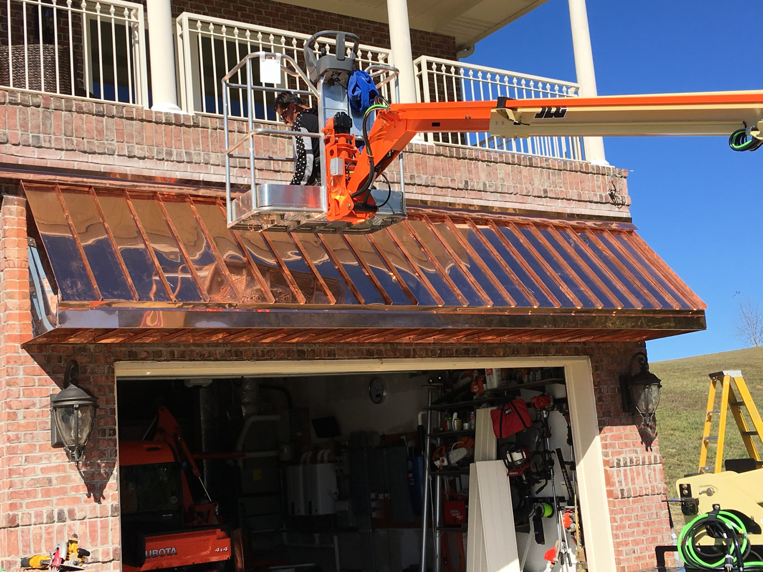 this is a picture of copper standing seam roof and our worker installing it on a boom lift in sharps chapel tn