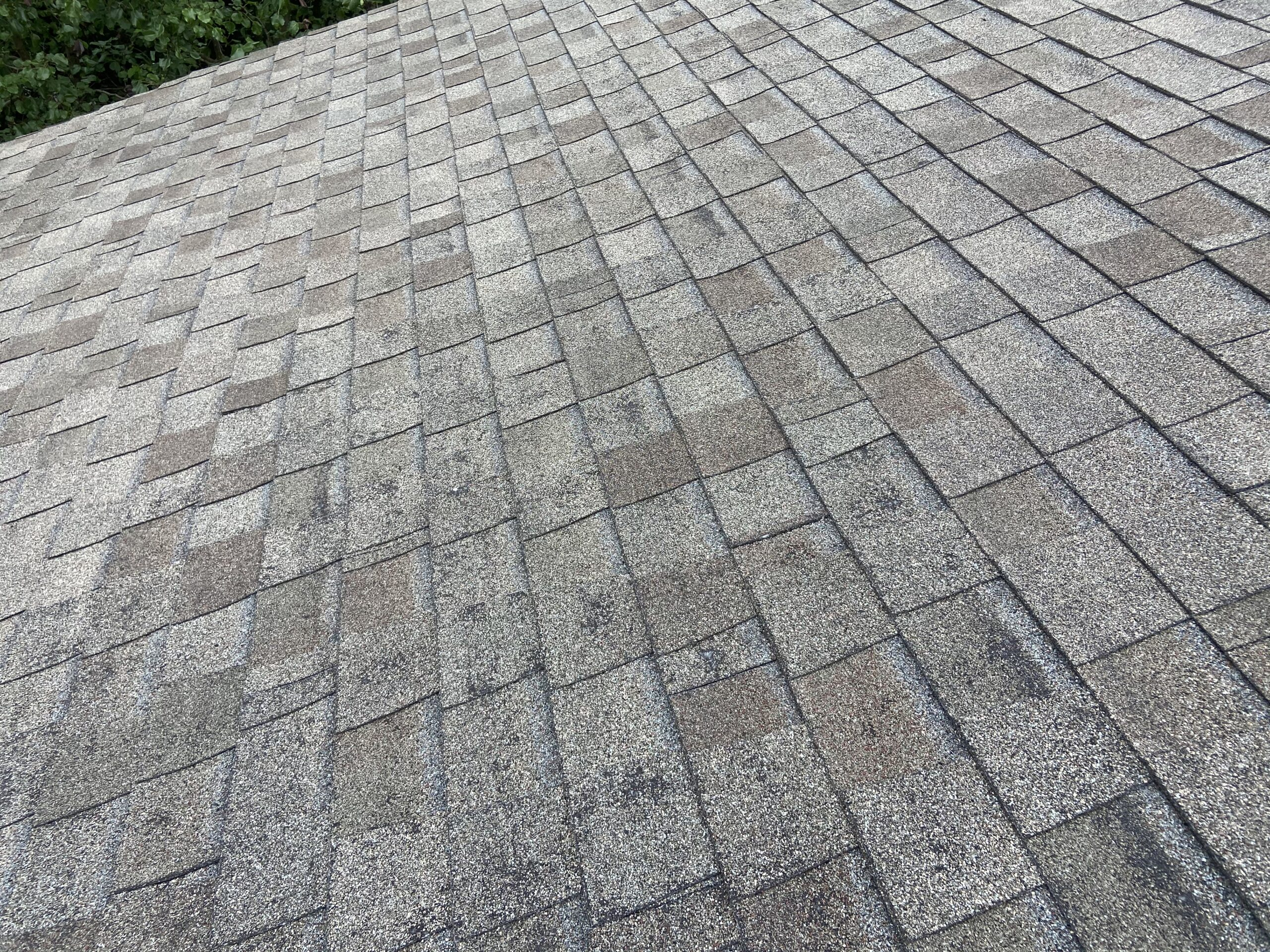 this is a picture of old weathered wood colored shingles that are blistering and in failure