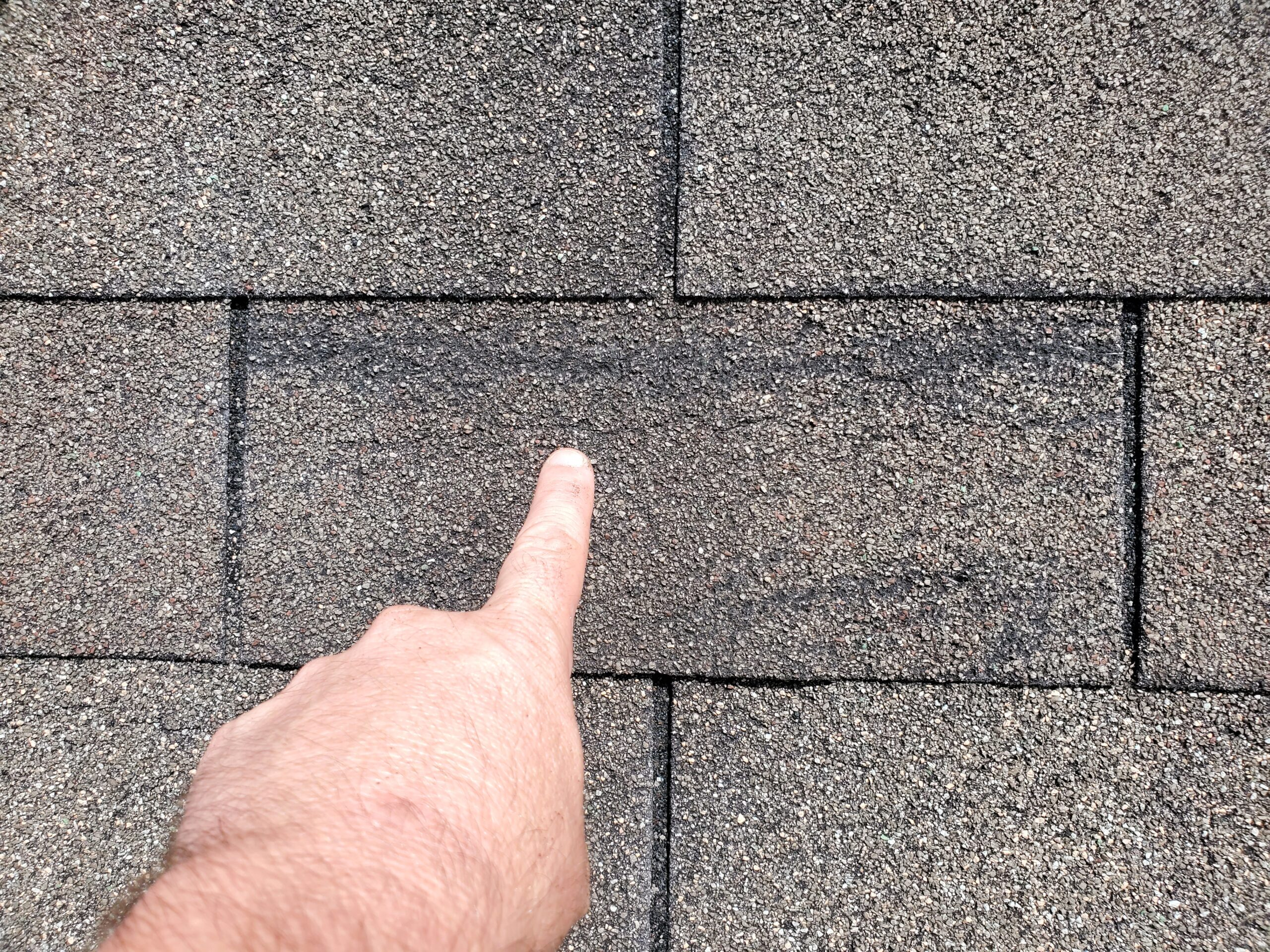 old 3 tab roof with wind damages to shingles