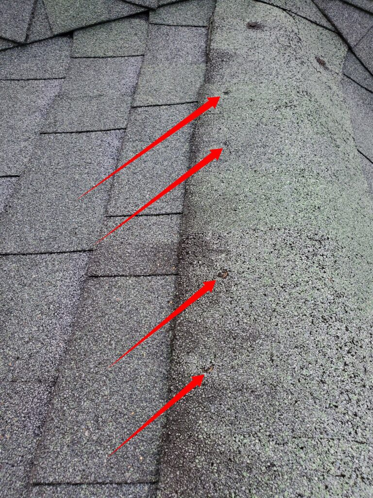 This is a picture of a grey shingle roof with nails pulling out of the shingle