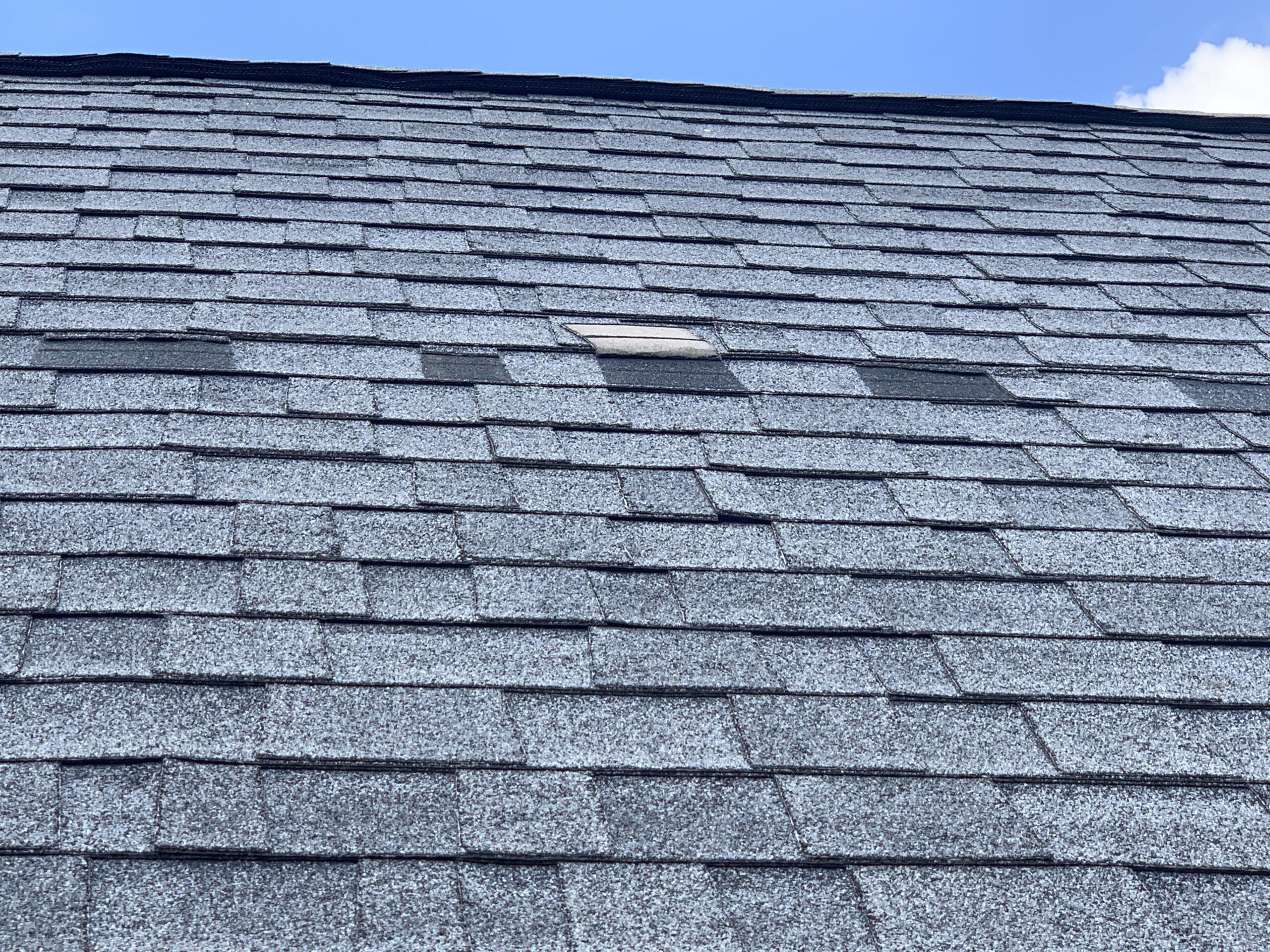 this is a picture of old gray dimensional shingles with missing tabs and missing shingles