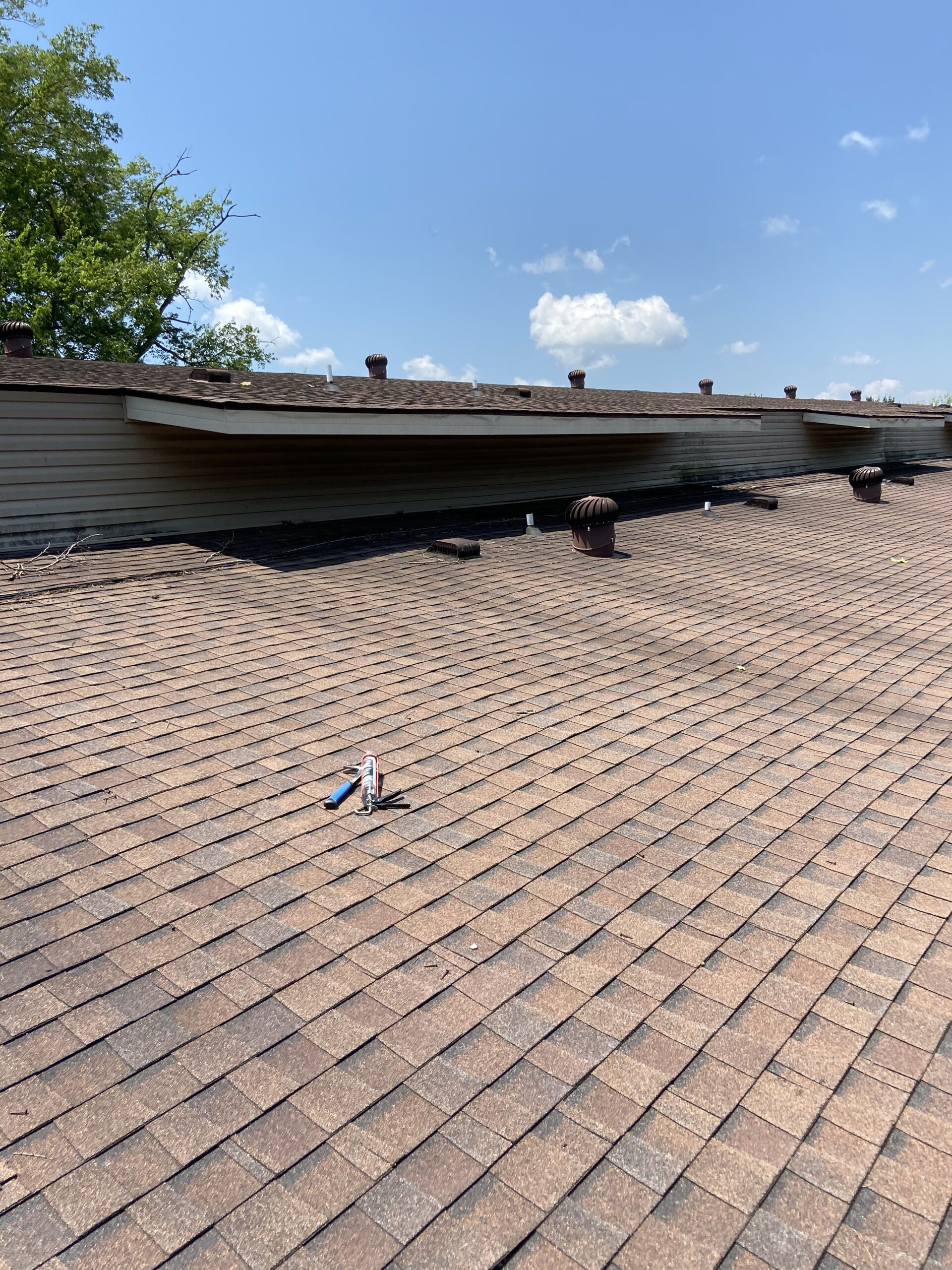 this is a picture of brown shingles on an apartment complex roof and the roof vents are in the picture