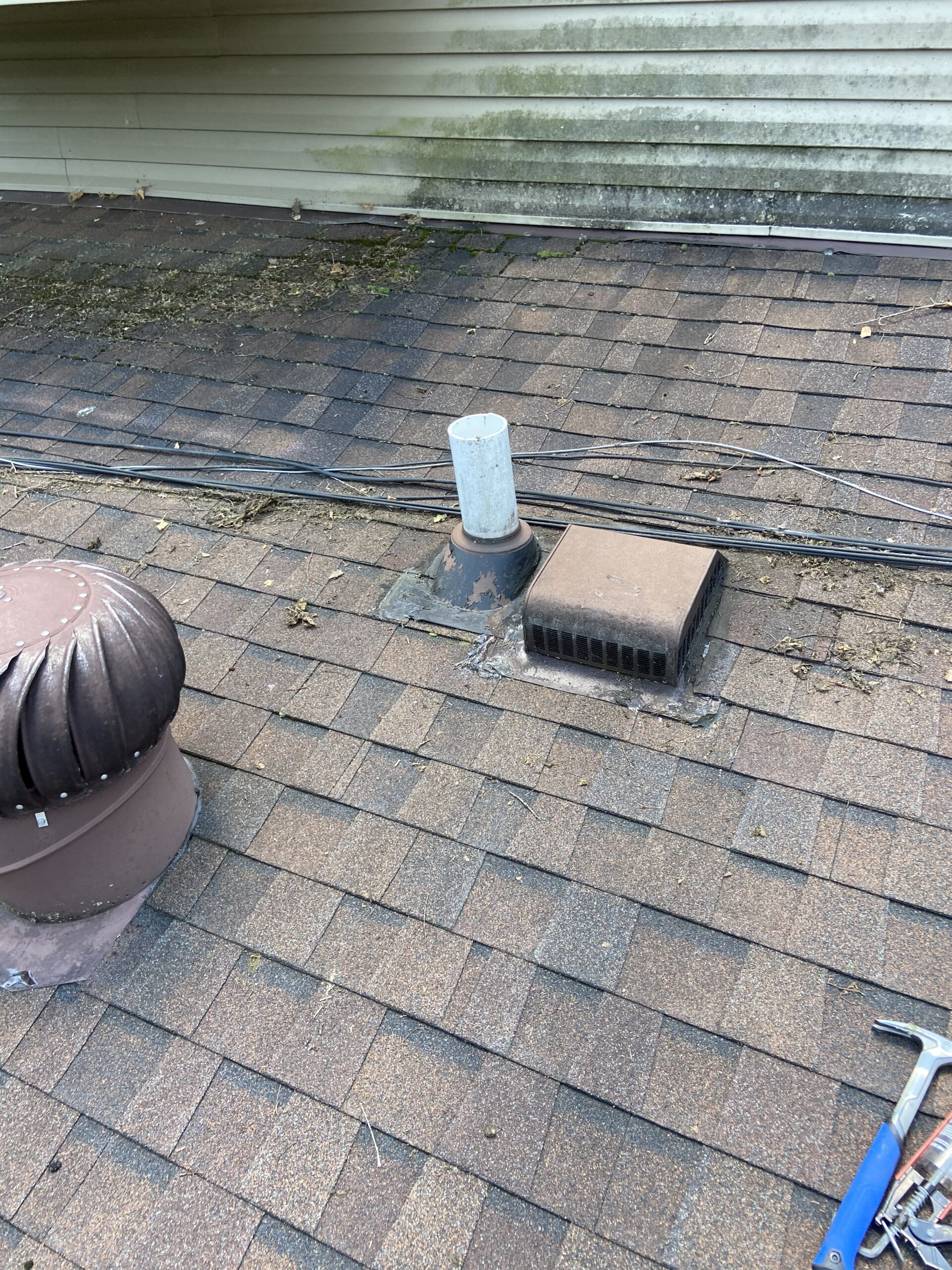 This is a picture of an area of a roof that is leaking there are bron shingles and pipes and vents coming through the roof