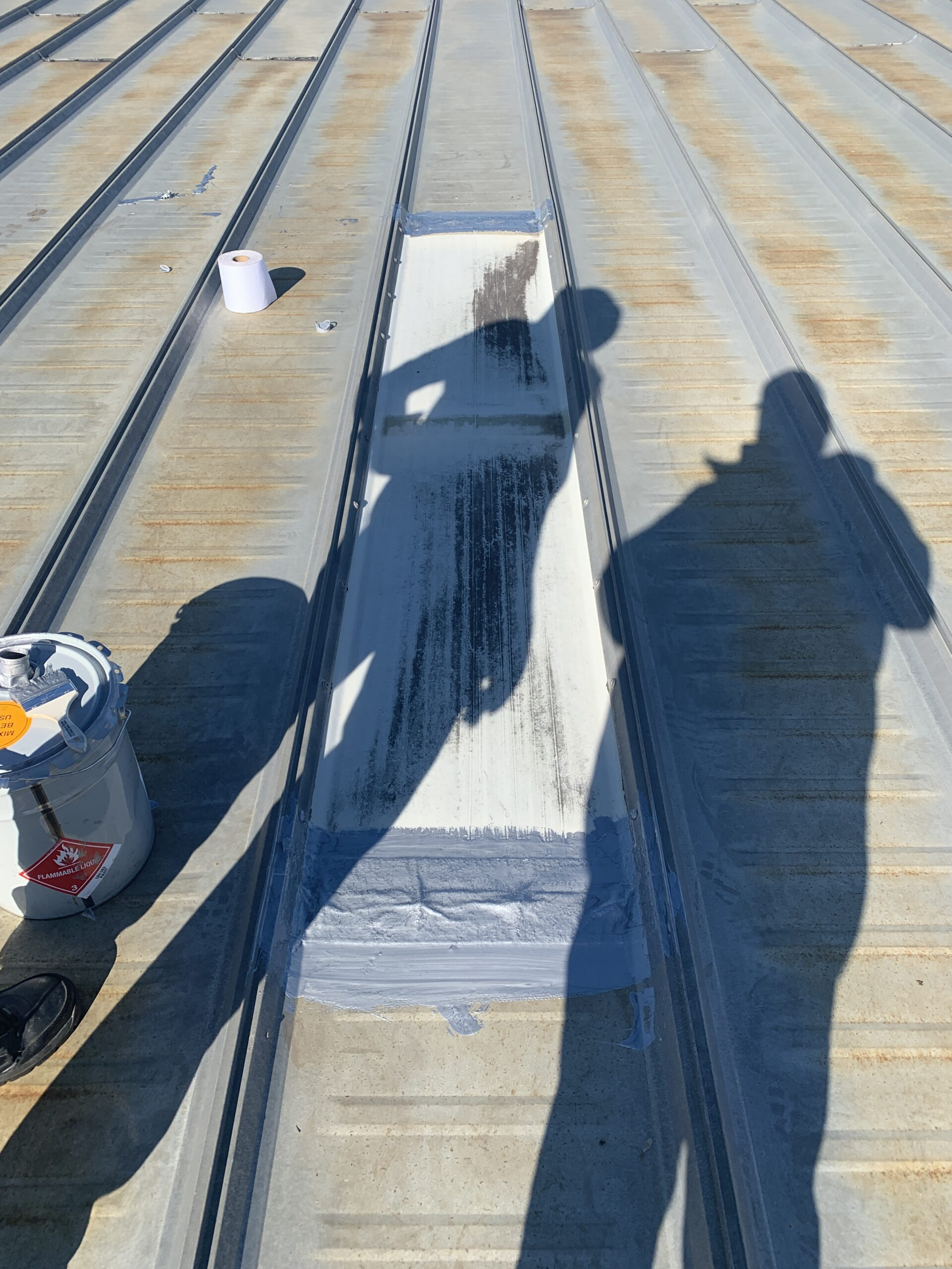 picture of commercial roof coating around a skylight on a metal roof