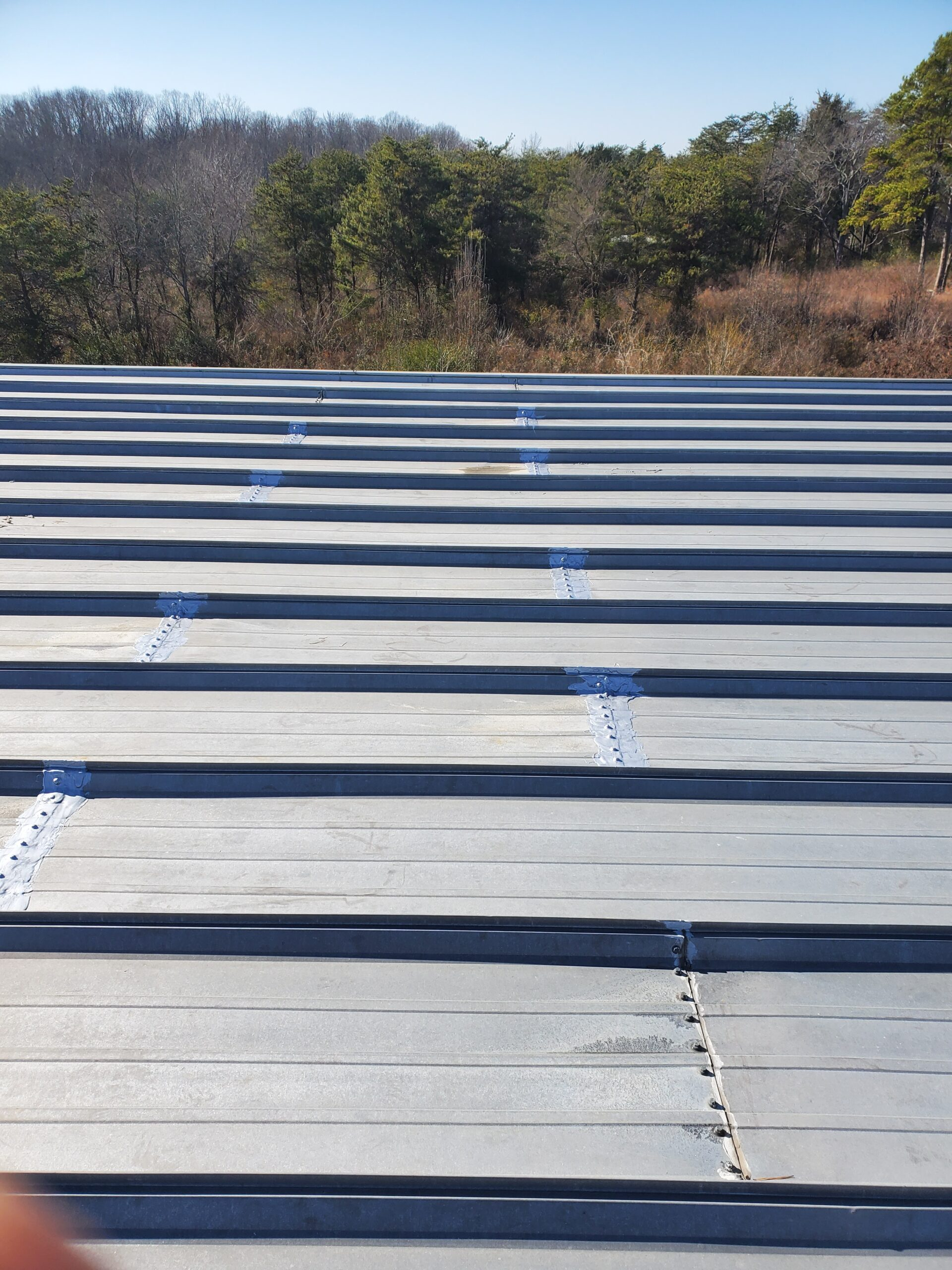 commercial roof coating a metal roof panel lap