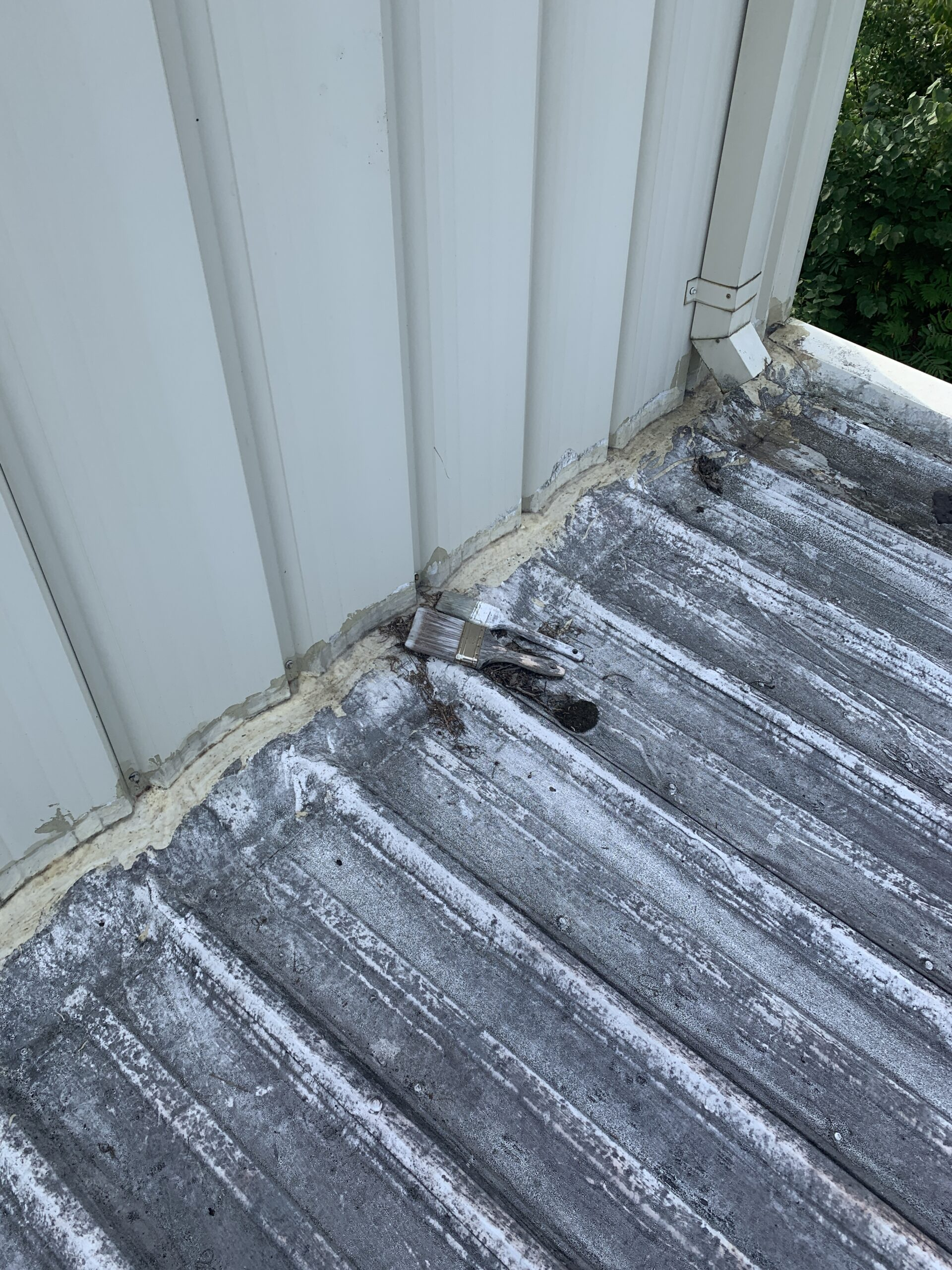 this is a picture of a gutter draining onto a the metal r panel roof and the flashing of the wall is in very bad shape
