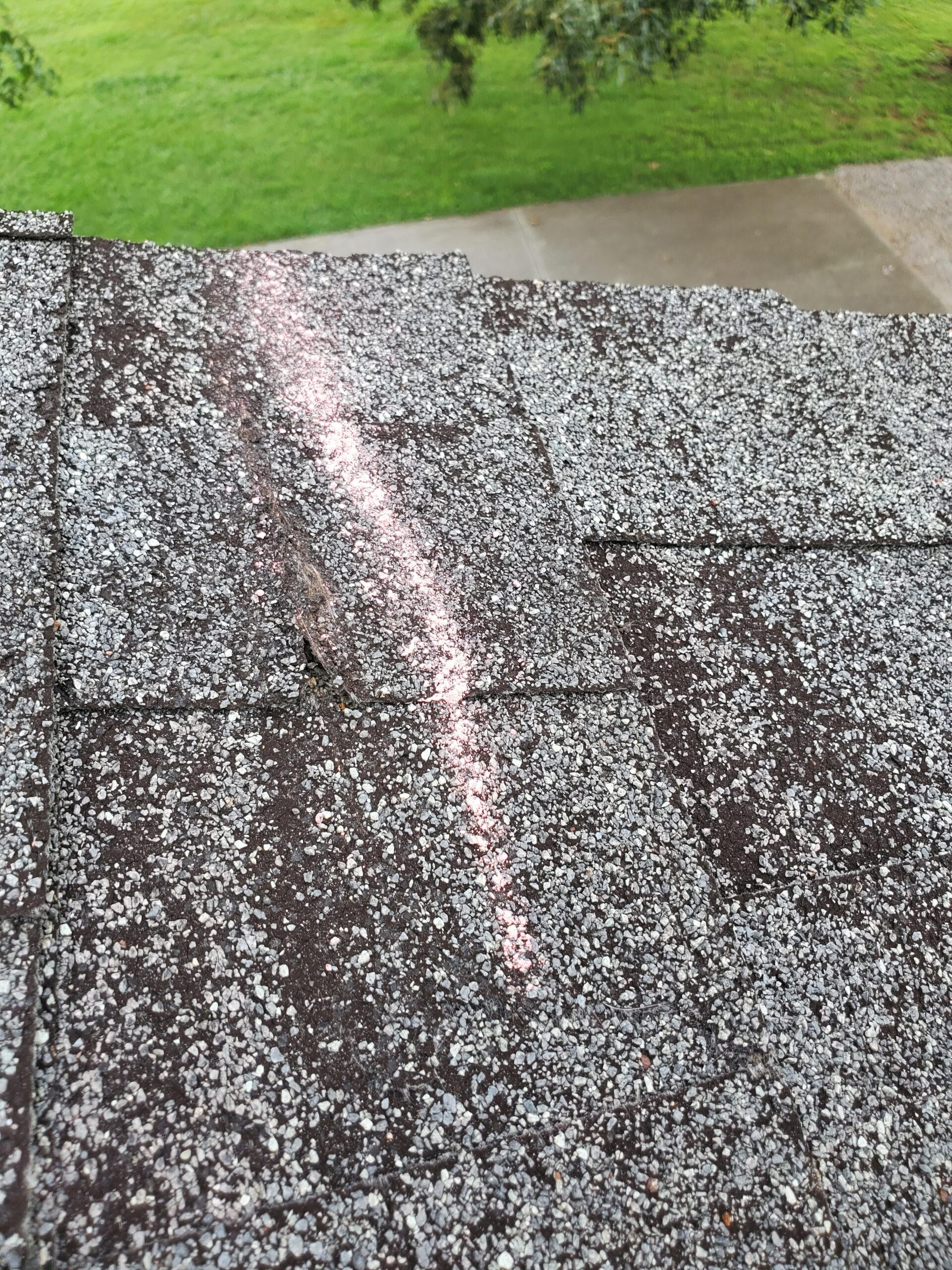 this is a picture of shingles that are wind damaged on the edge of a roof