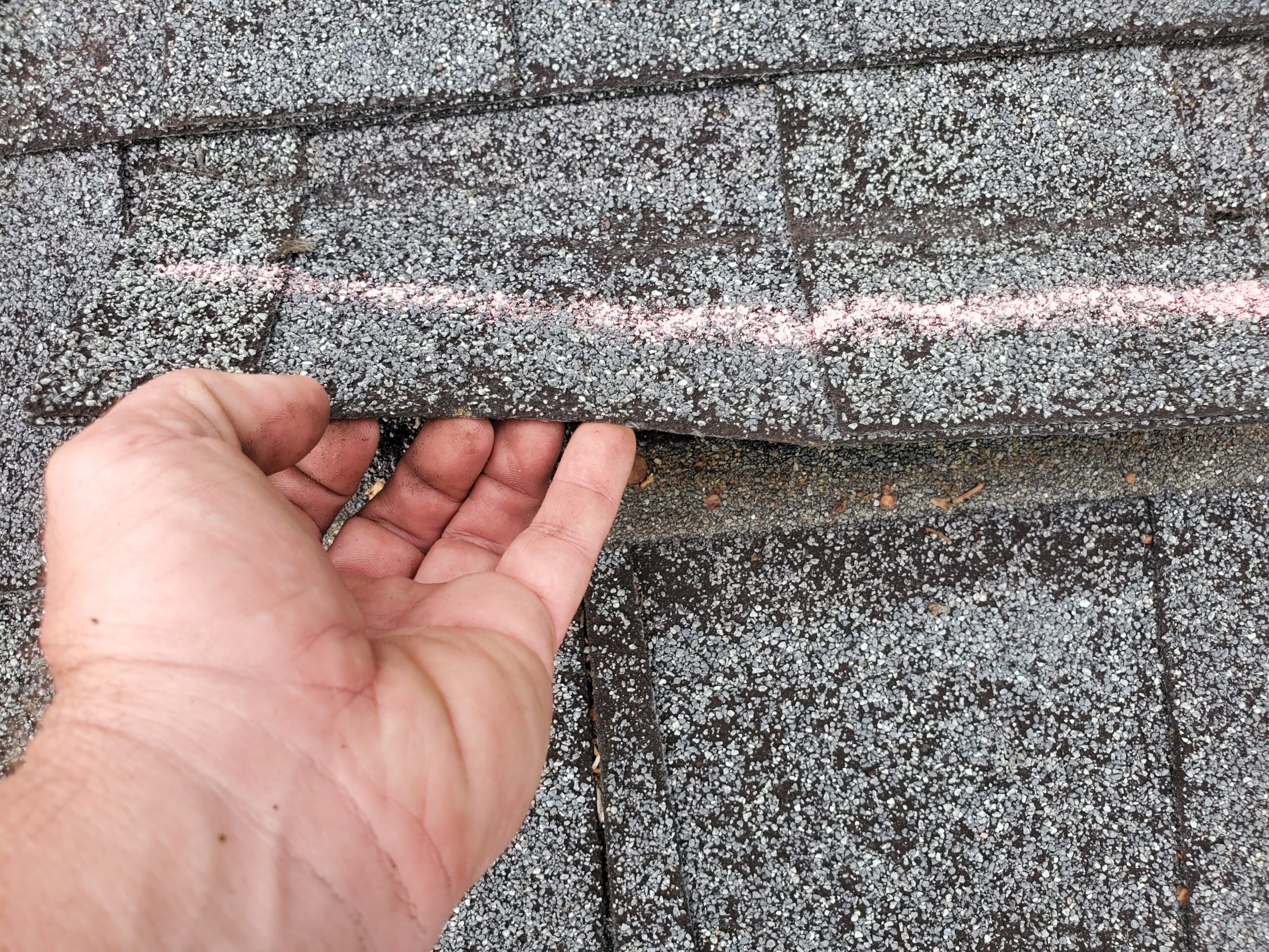 another wind creased shingle that is marked for an insurance adjuster to see