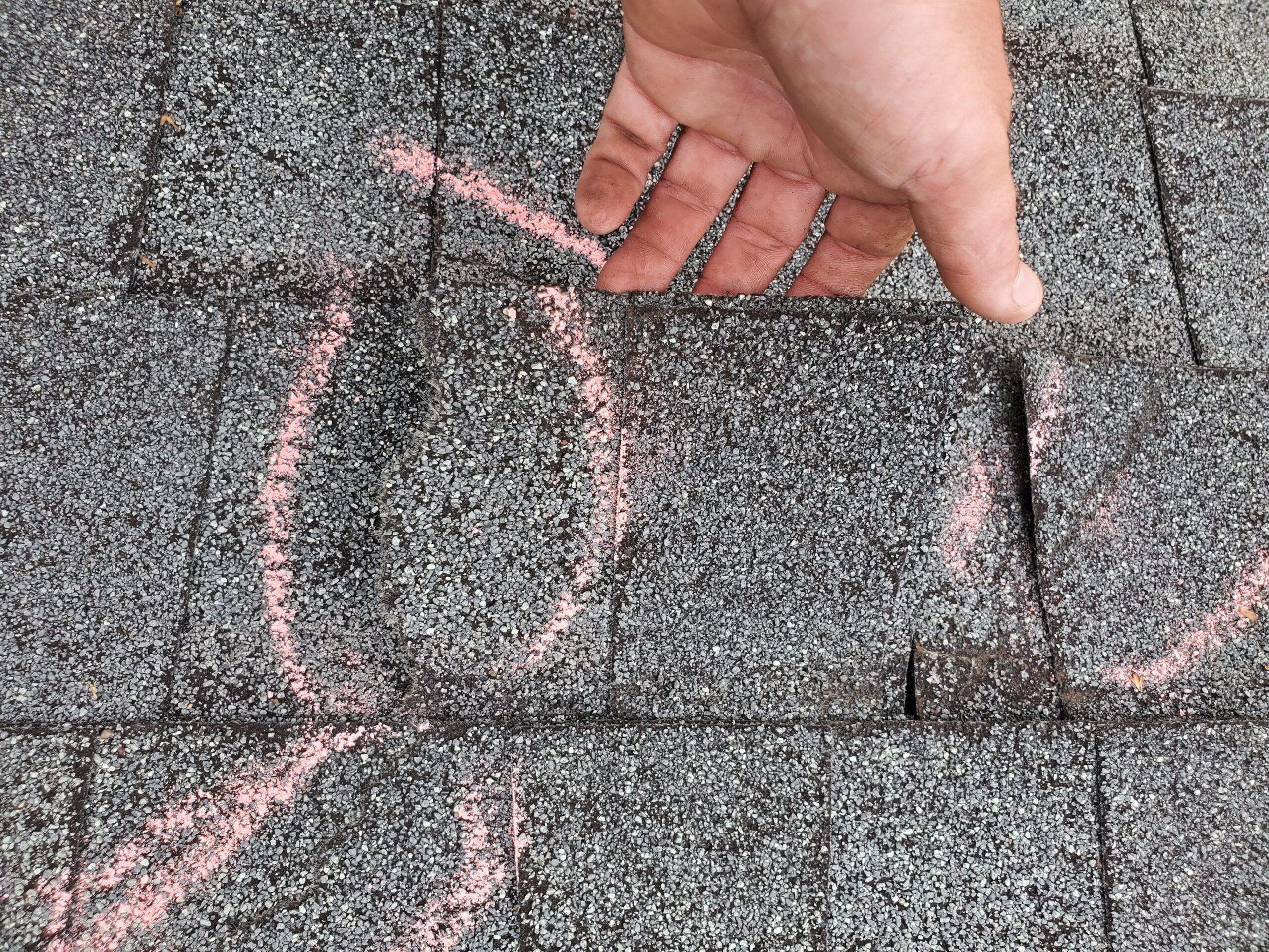 these chalk marks shown in the picture are there to show an insurance adjuster shingles broken by storm damages