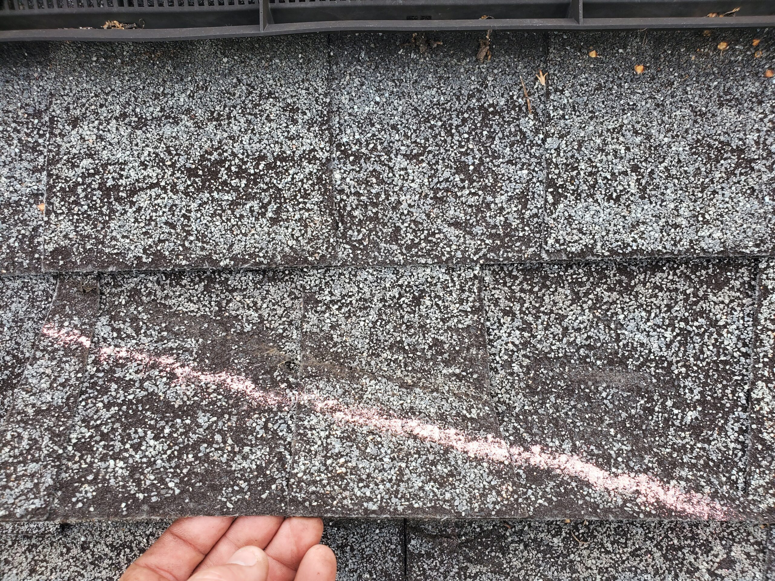 this is a picture of another chalk line on this roof showing wind damages to the shingles