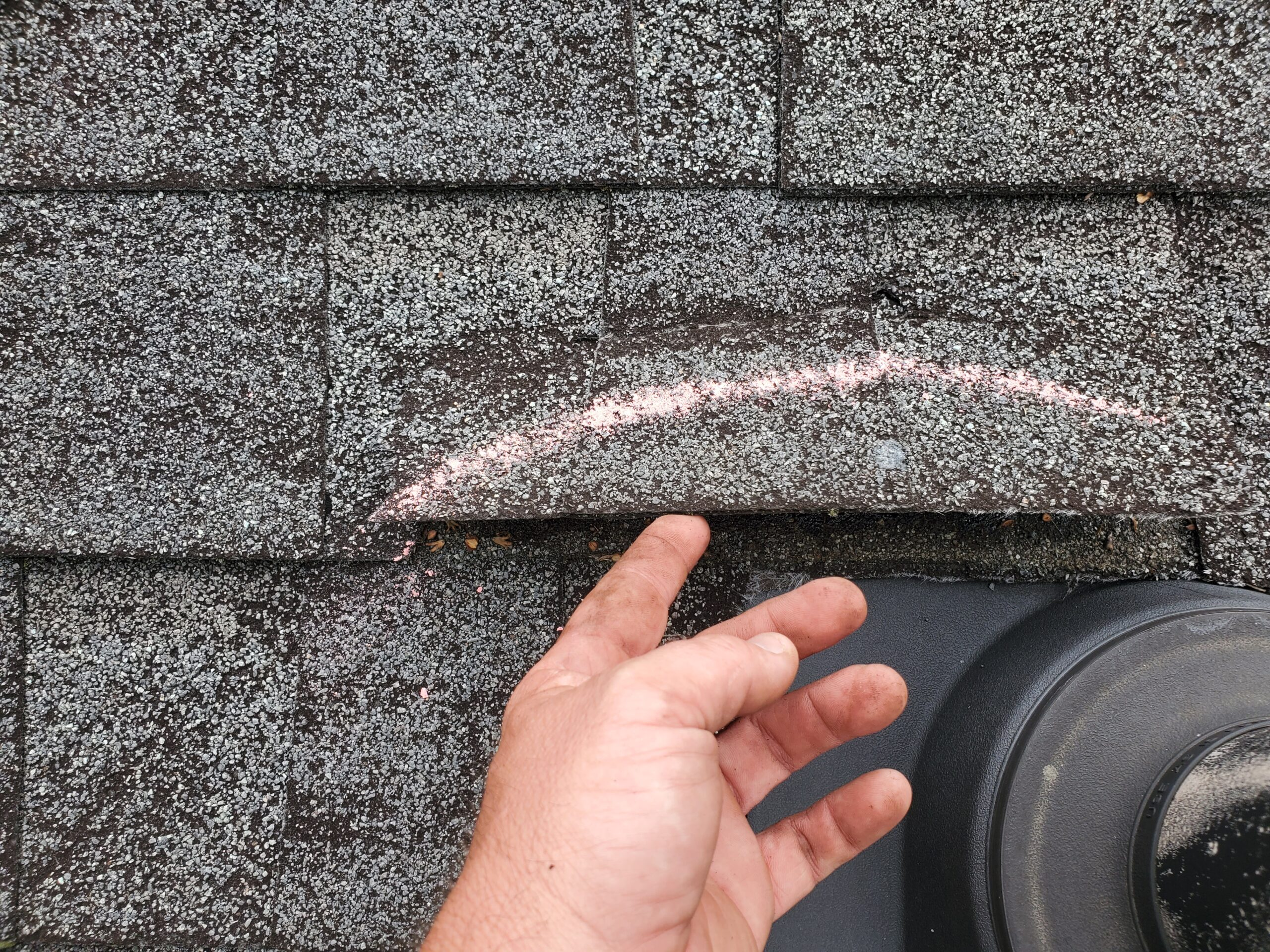 this is a picture of chalk marking a wind damaged shingle and someone lifting this shingle up