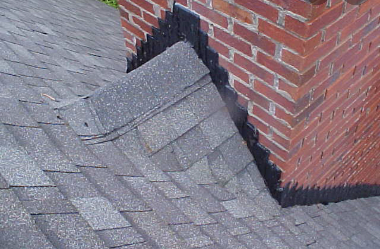 this is a grey colored shingle roof meeting a brick chimney in knoxville tn