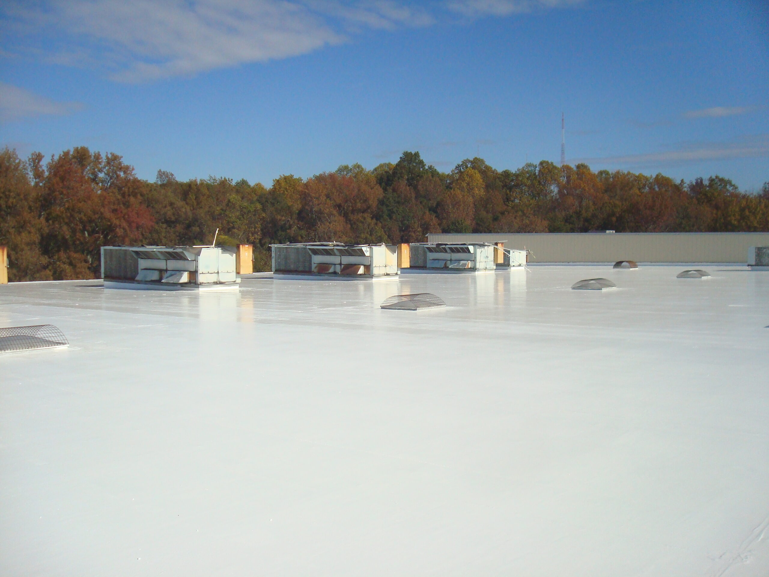This is a white flat roof with unites and vents being shown.
