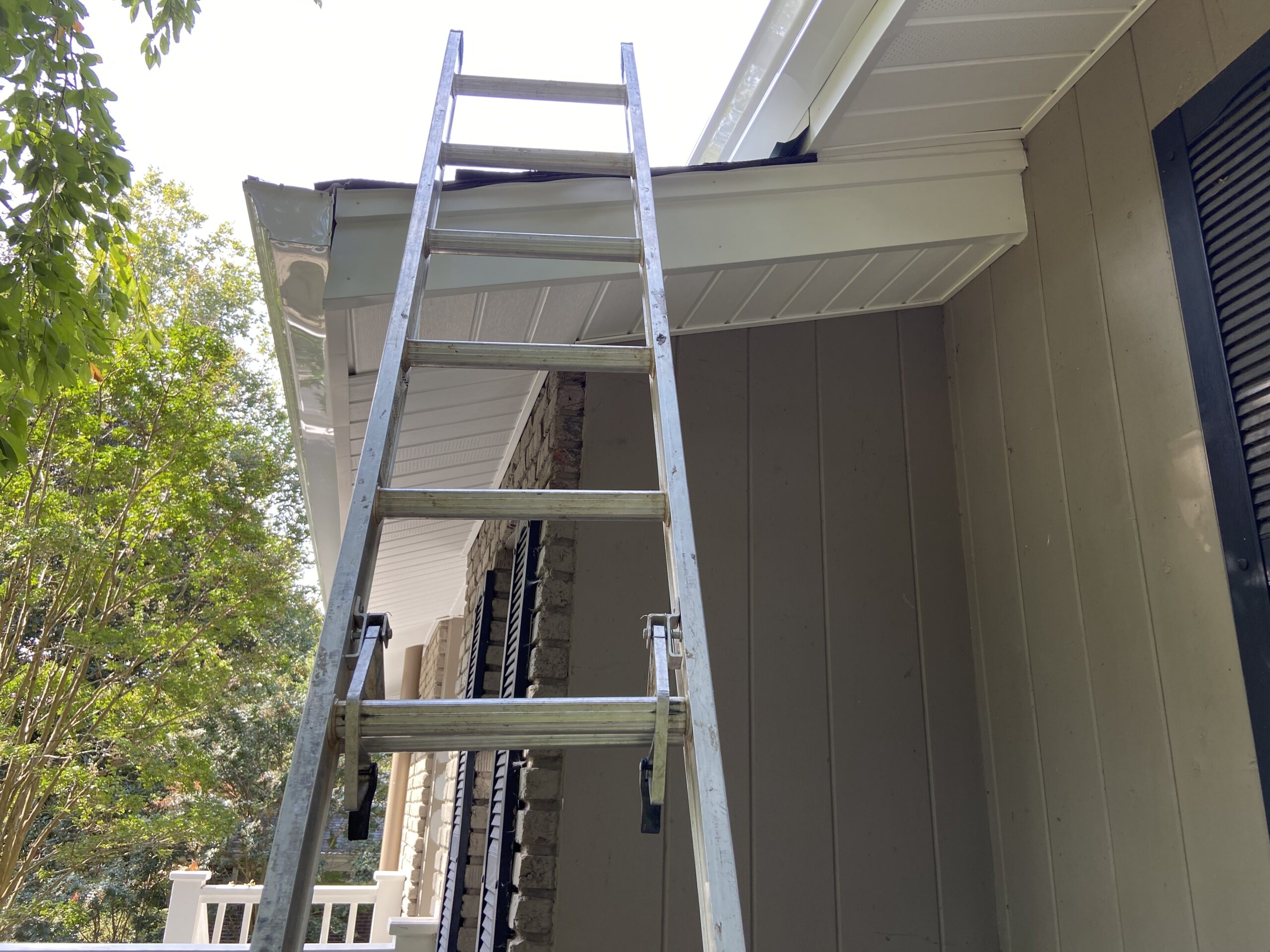 This is a picture of the new soffits they are white and color and there is a ladder in the foreground