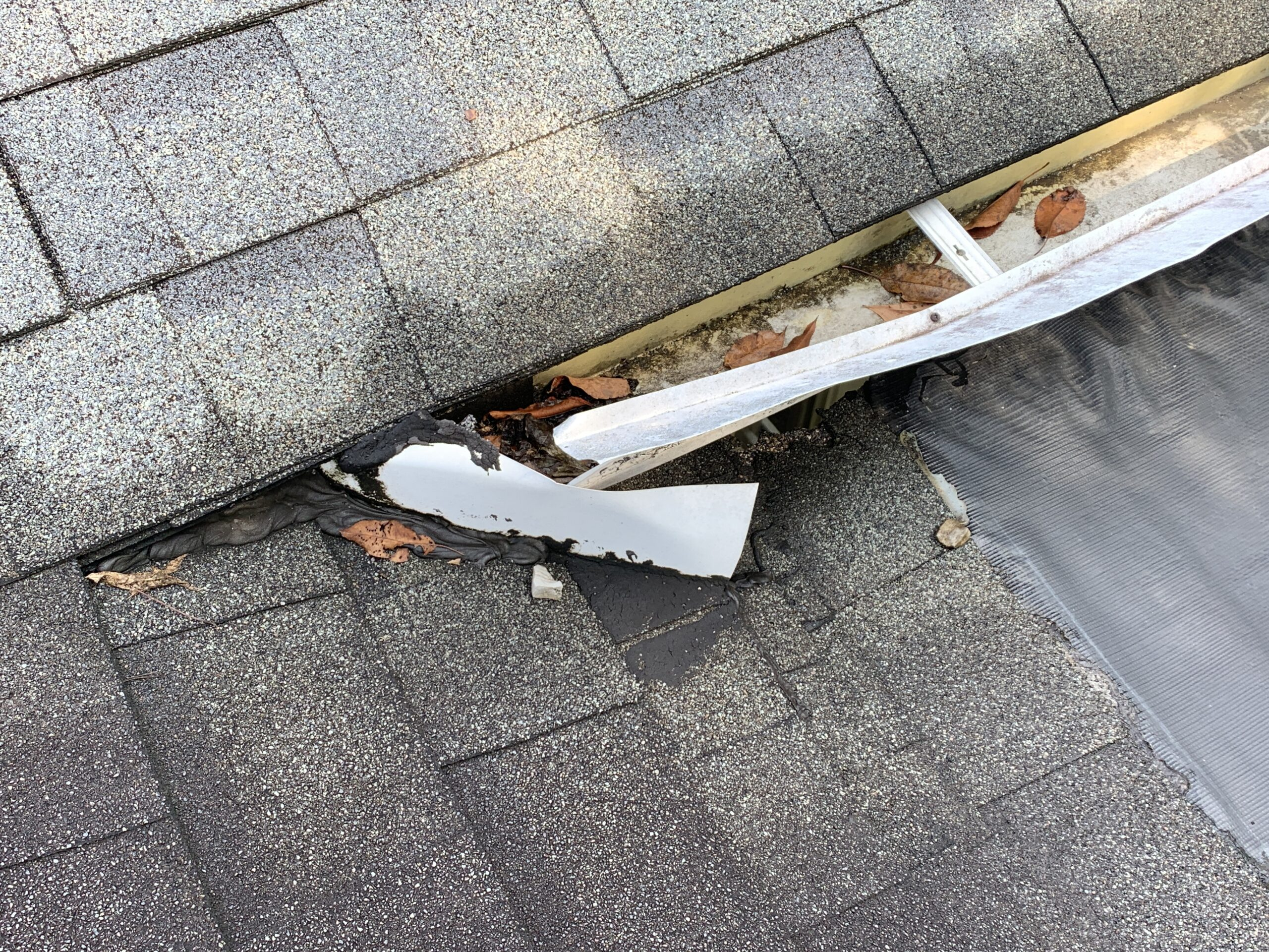 In this photo you can see that there have been some attempts to divert water from the main problem area on the flat roof adjoining to an old shingle roof. The gutter leaks and the membrane leaks and has caused severe water damage to the porch structure underneath