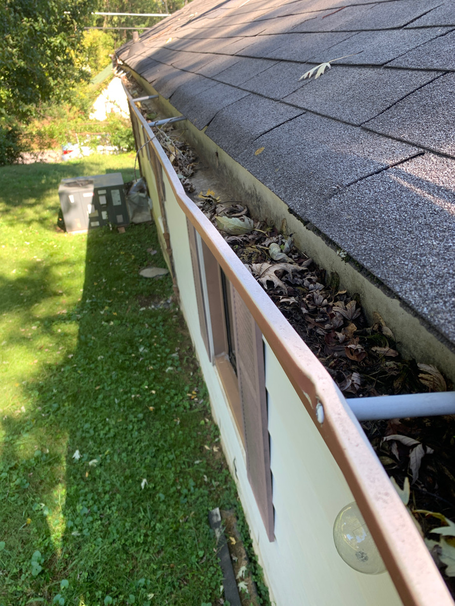 This is a view of white gutters that have leaves and debris in the gutters.