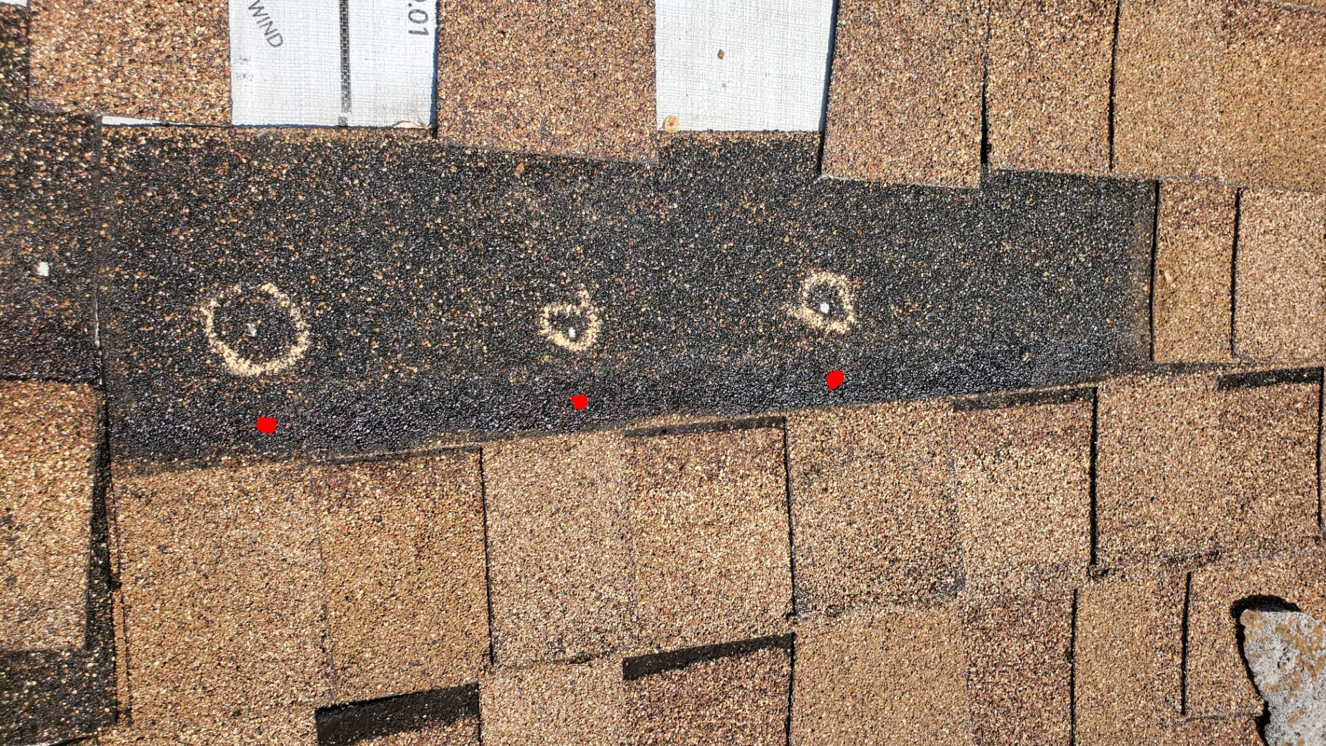 In this picture there are circles Drawn on a shingle showing where the nail holes are at.