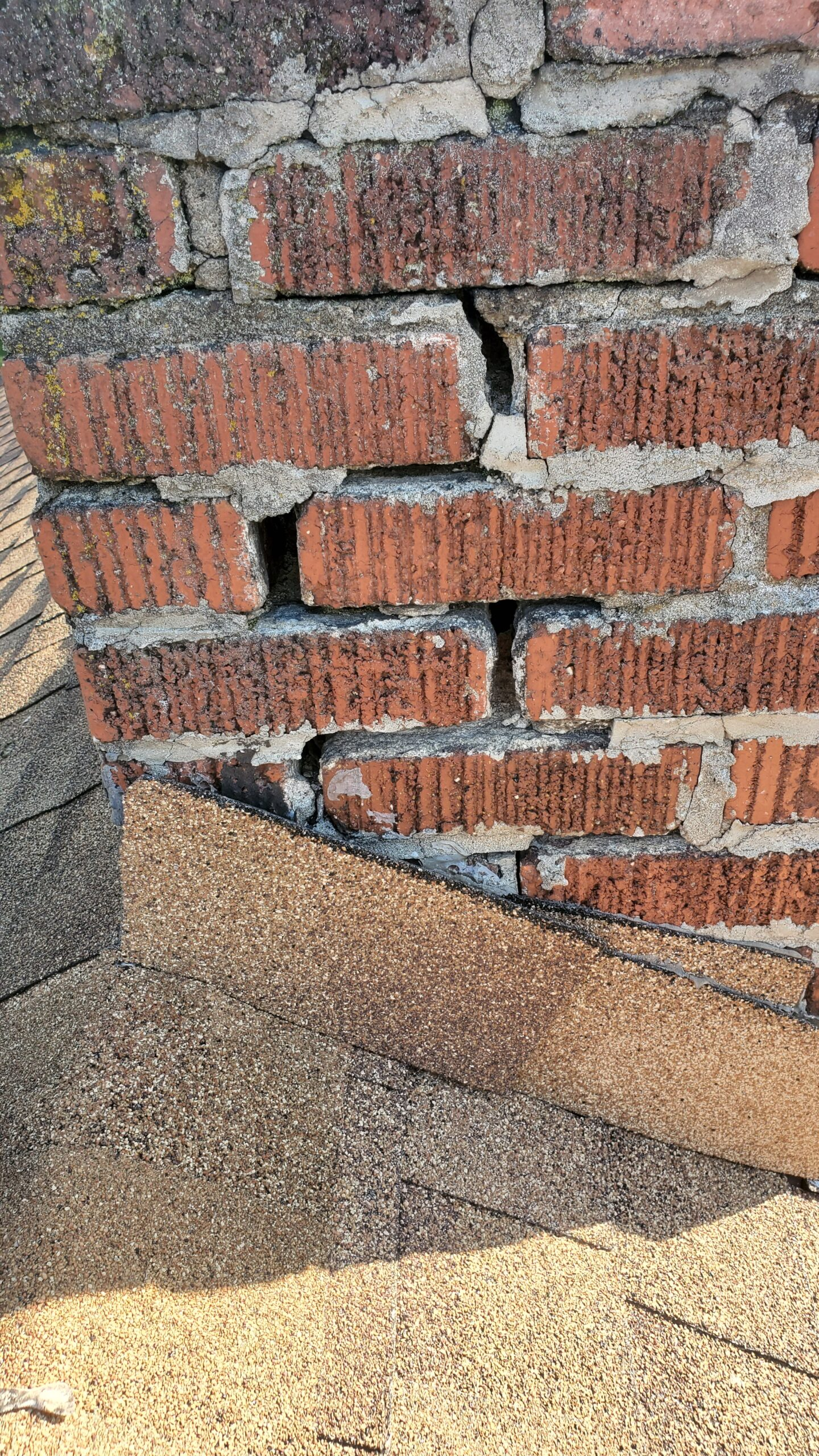 This is a picture of a small brick chimney on a roof and the bricks are starting to come apart and mortar is coming out between them