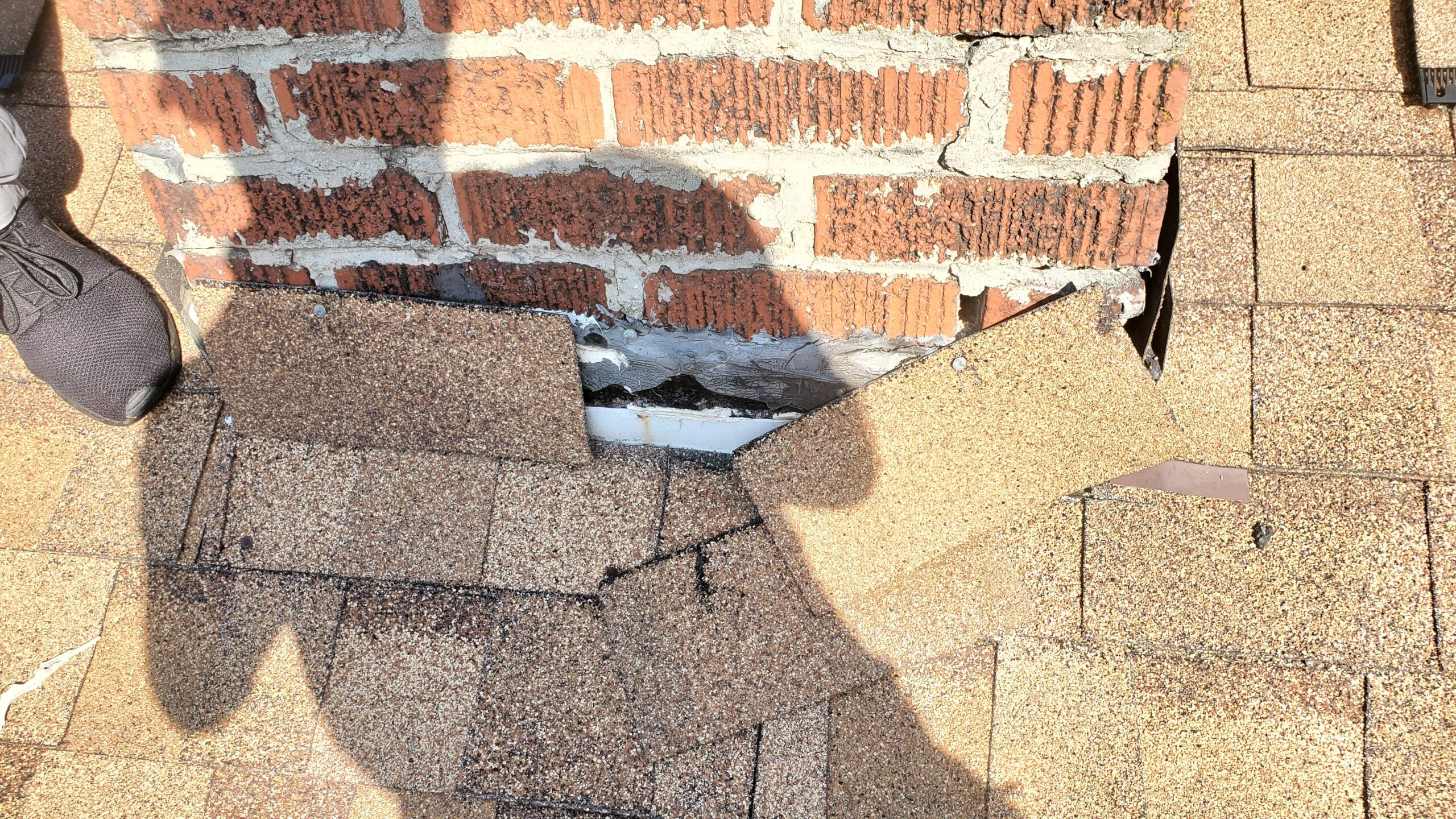 This is a picture of a smalle chimney that has shingles around the bottom of it in place of metal flashing