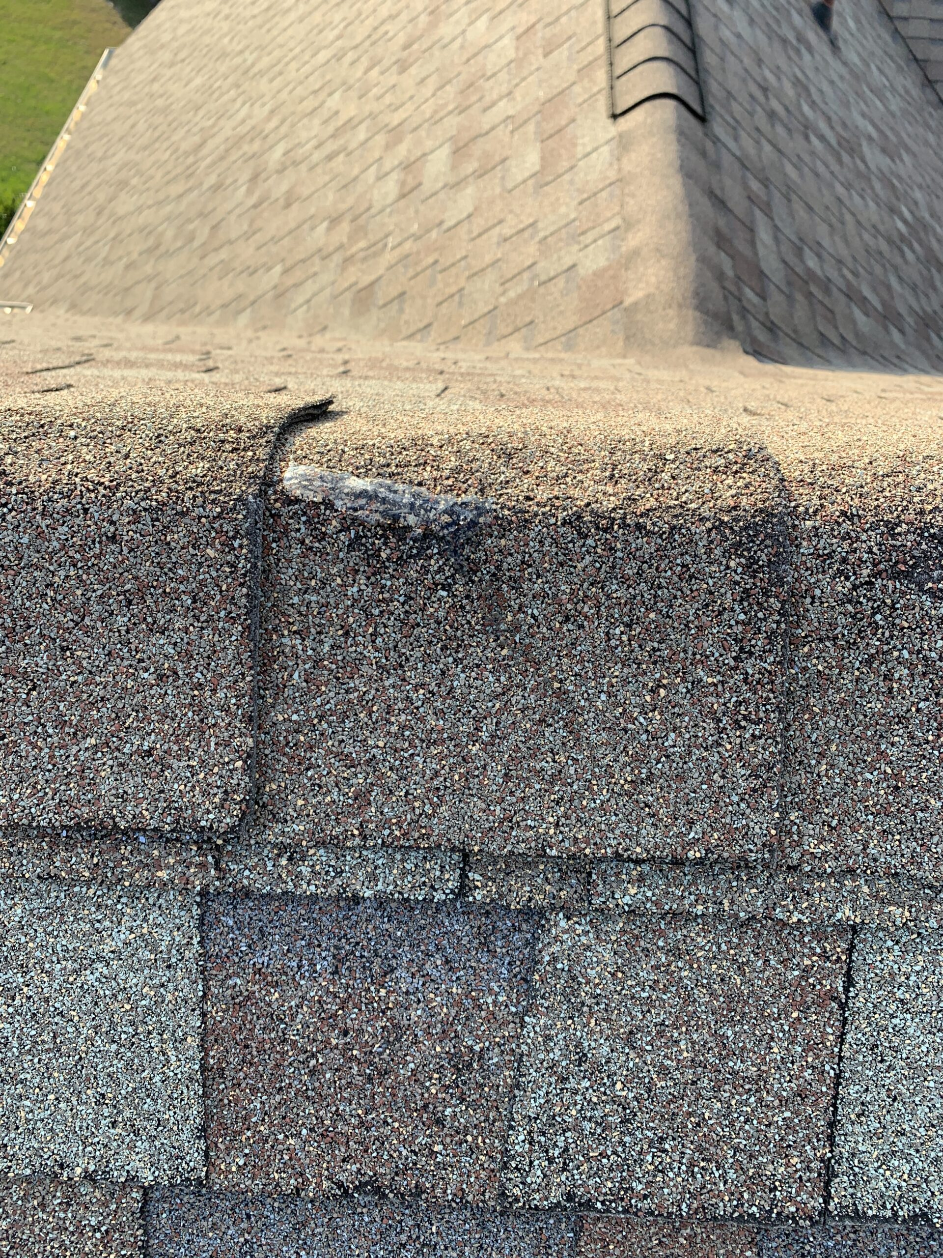 A hole from some type of impact on the ridge cap shingles is likely to cause a leak on the very top of the roof. This will need to be sealed or replaced