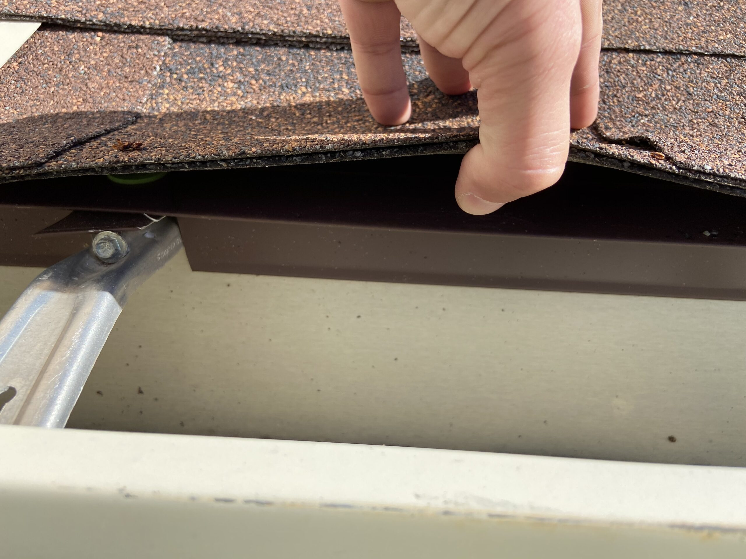 This is a picture of brown drip edge at the eve of the roof for the gutters are