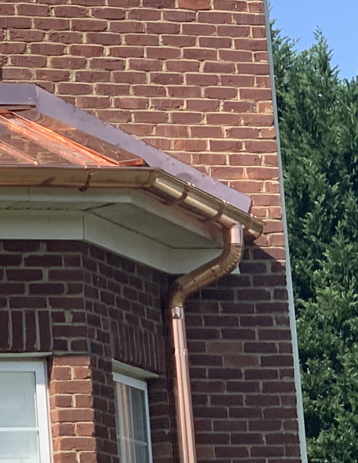 Handmade standing seam copper roof and half round gutters downspouts and hangers on a bay window