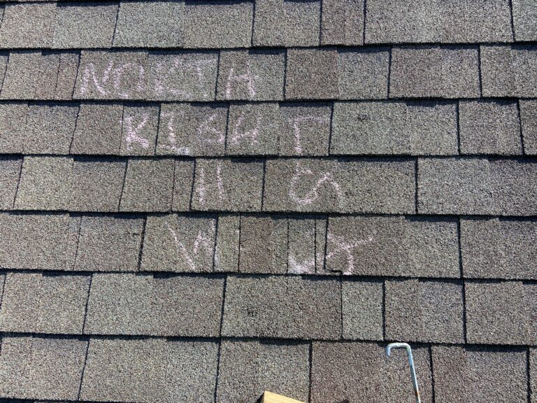 Adjuster's chalk marks on a shingle roof saying there's no damage to the roof