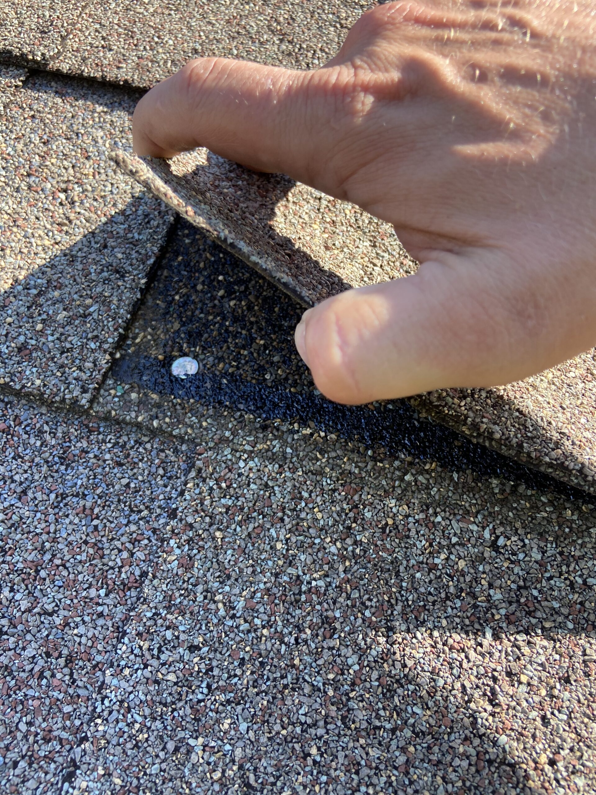 This is a picture of a nail that is miss placed on a shingle roof it is too close to the shingle union