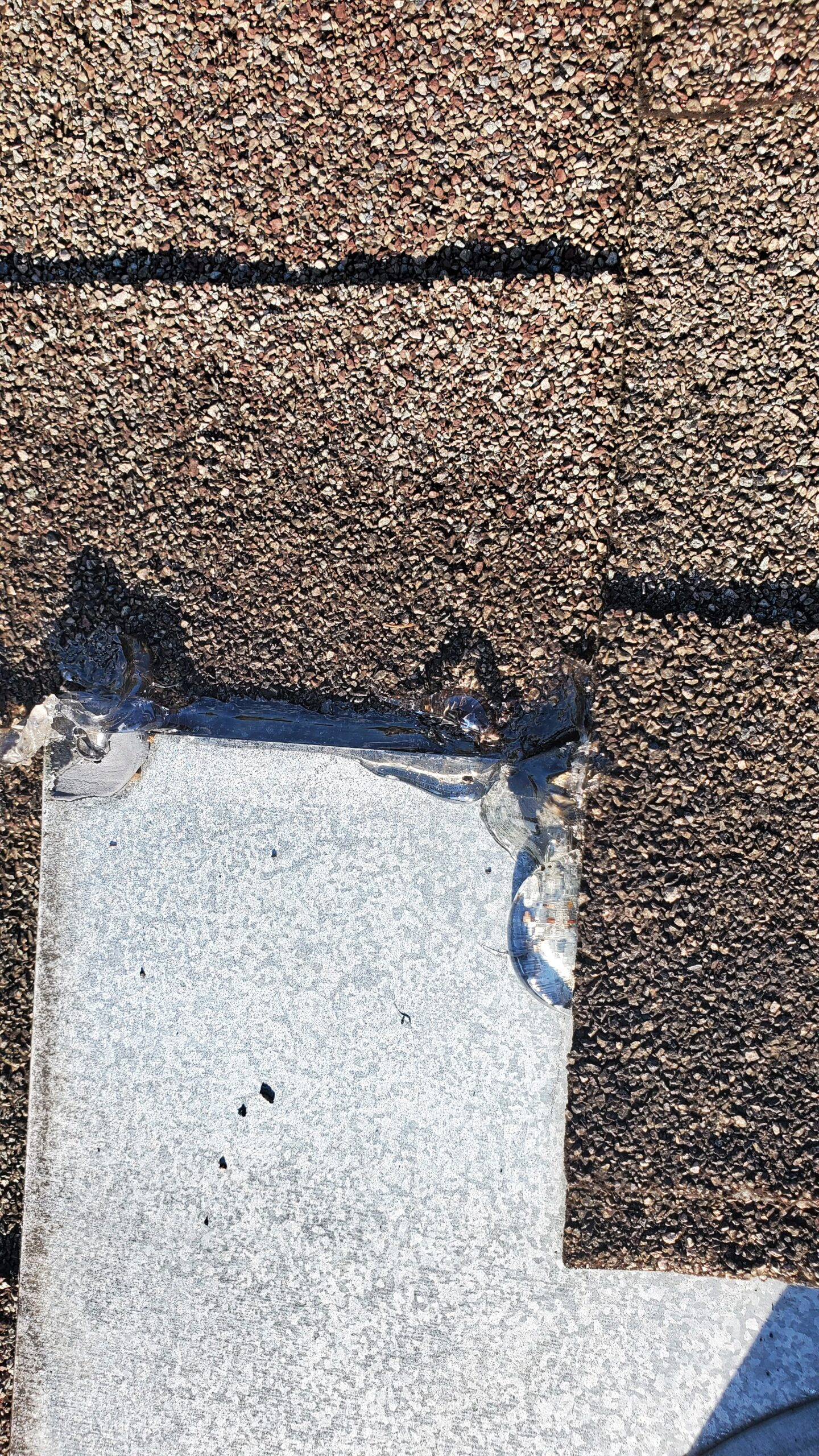 This is a picture of exhaust vent coming out of a roof. This vent has clear caulk along the edges.