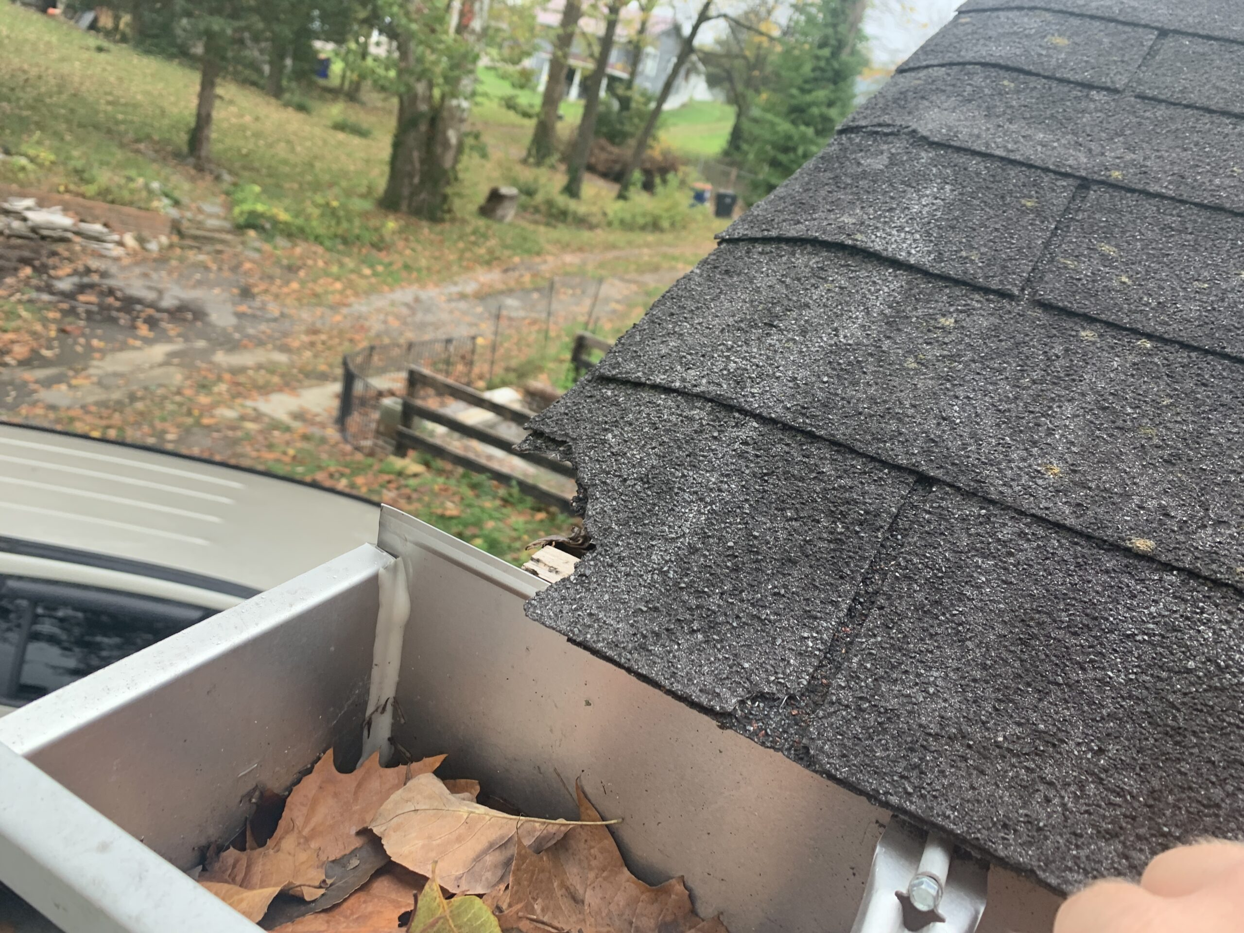 Brittle in broken shingles on an old three tab shingle roof in Knoxville Tennessee