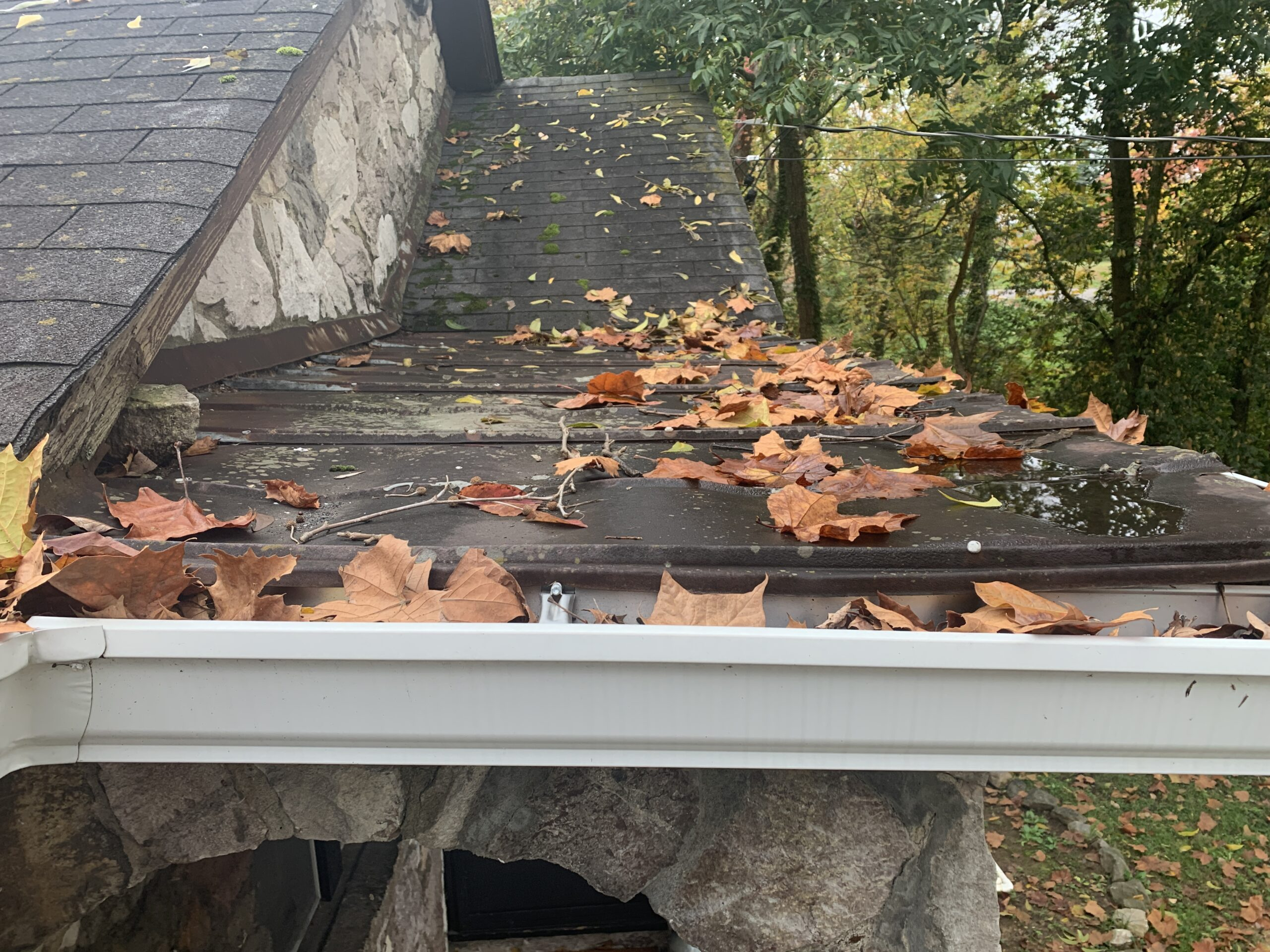 Metal roof over flat portion incorrect materials on a house in Knoxville Tennessee old three tab shingles