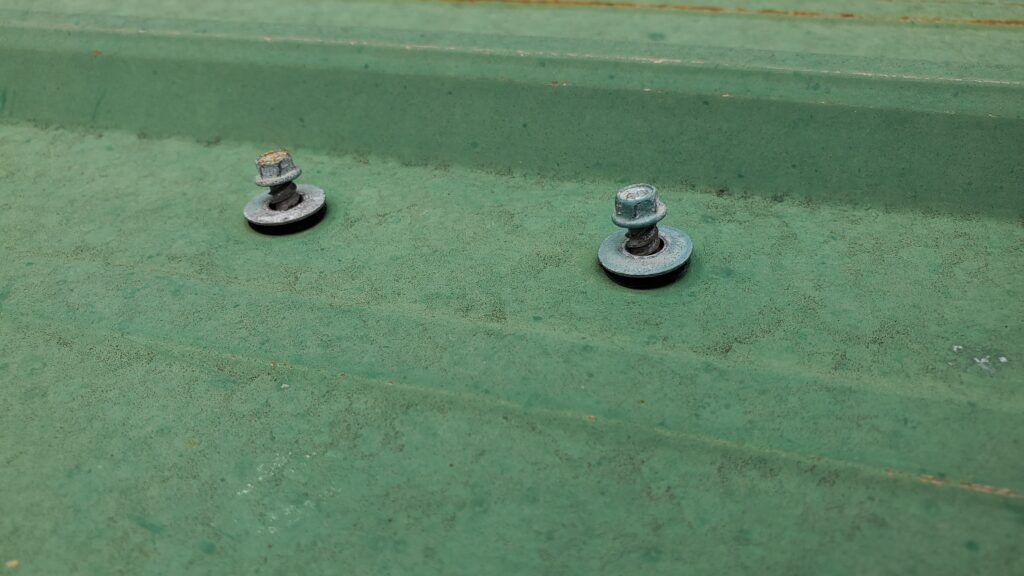This is a picture of screws on a green metal panel.