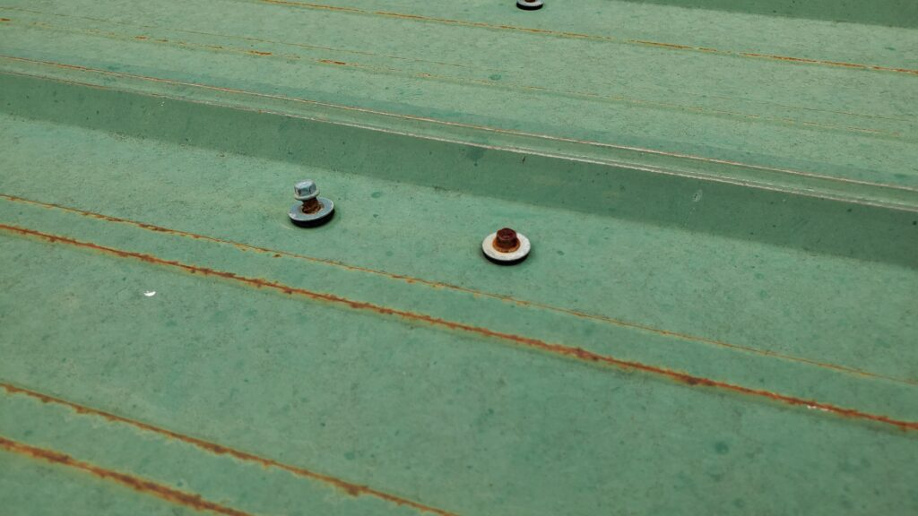 This is a picture of a loose screw on a green metal panel with rust.