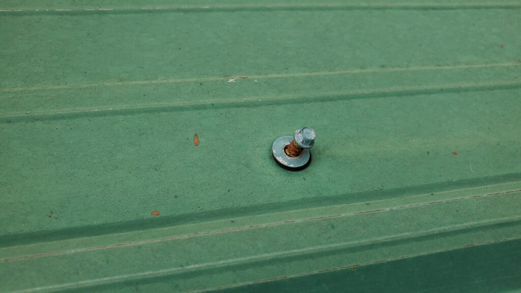 This is a picture of a loose screw on a green metal roof.