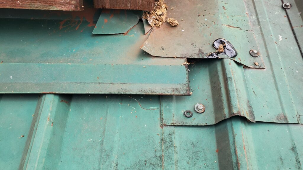 This is a picture of a green metal roof with loose screws and damaged wood.