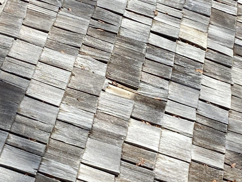 More cedar shake shingles that are missing on a roof