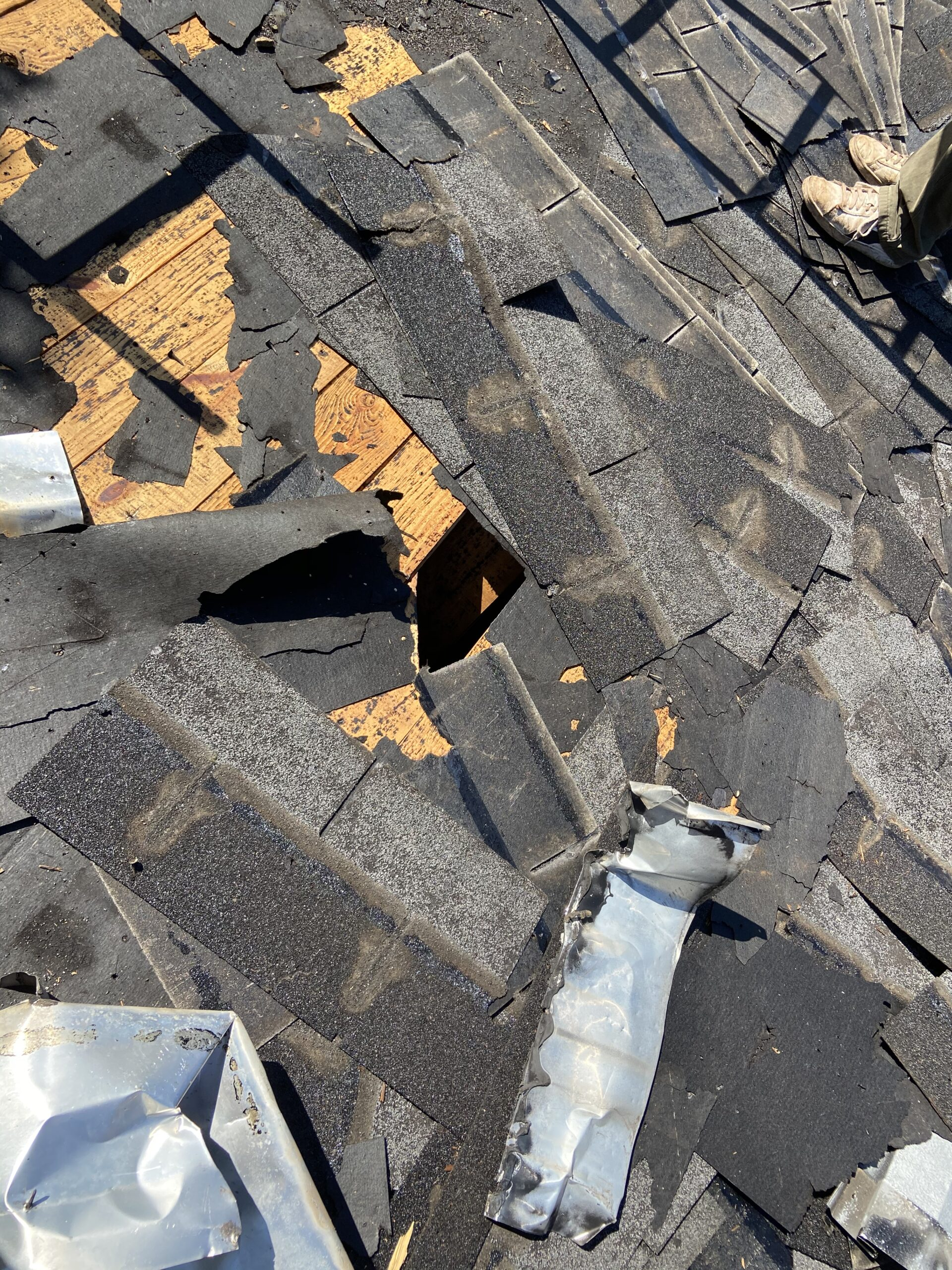 This is a picture of shingles being torn off the roof and a hole in the roof decking