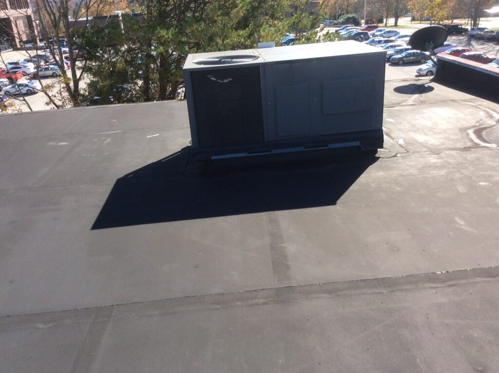 This is a view of a commercial flat roof with an AC Unit.