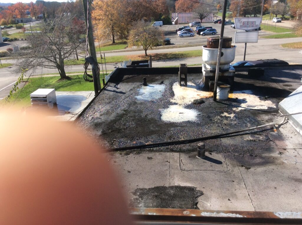 This is a view of a commercial flat roof with damaged areas.