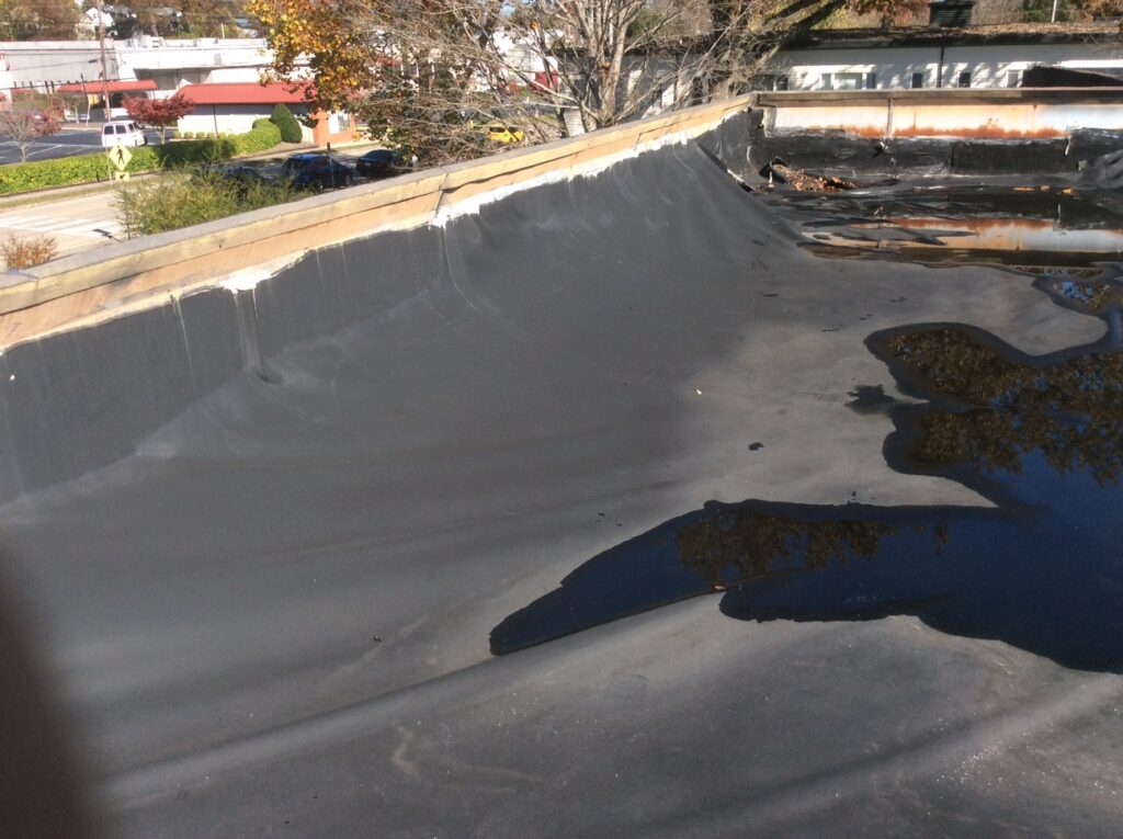 This is a view of a commercial flat roof with ponding water.