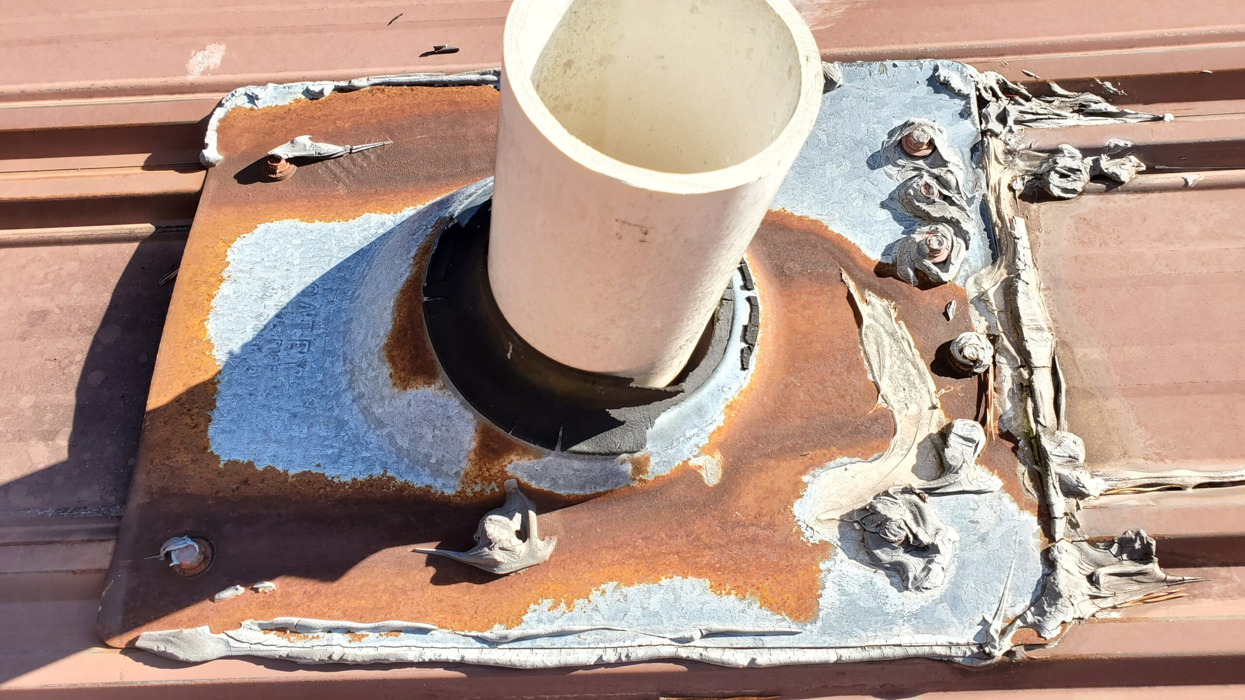 This is a picture of the old rusted pipe boot on top of a metal roof