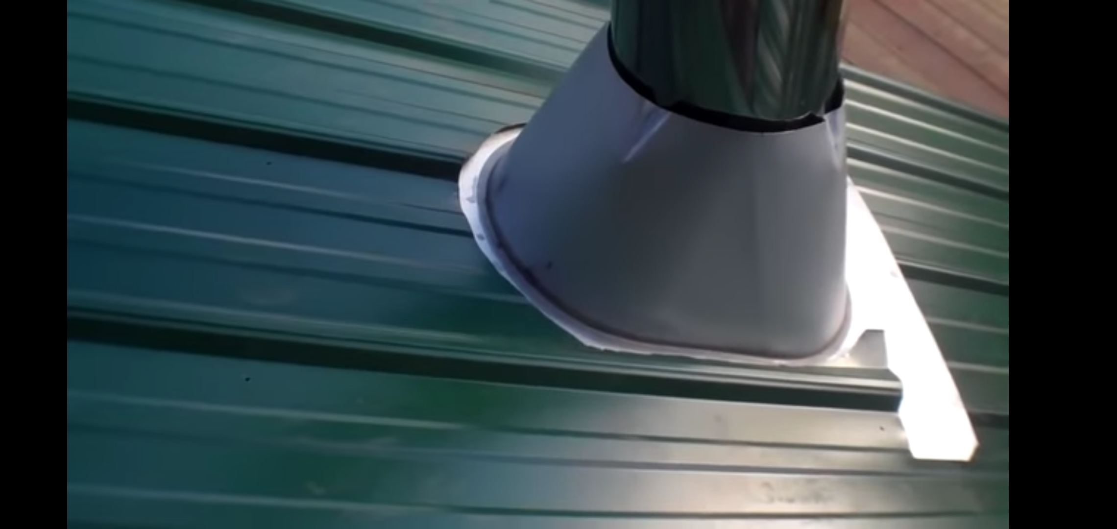 This is a picture of a metal chimney vent coming through a green metal roof. This is the proper way to install it with the top under the metal.