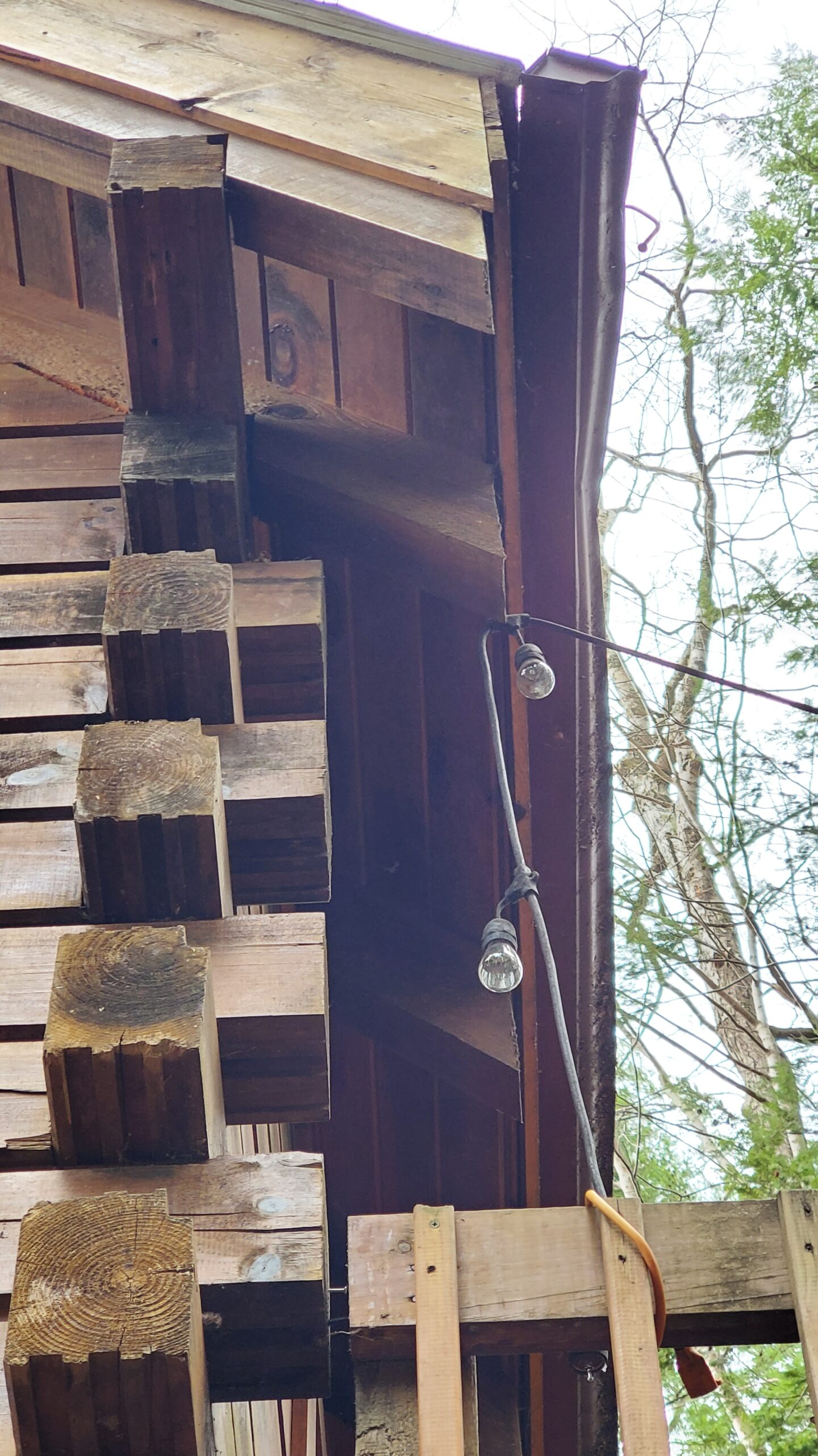 This is a picture taken from the ground of a section of gutter on a wood cabin