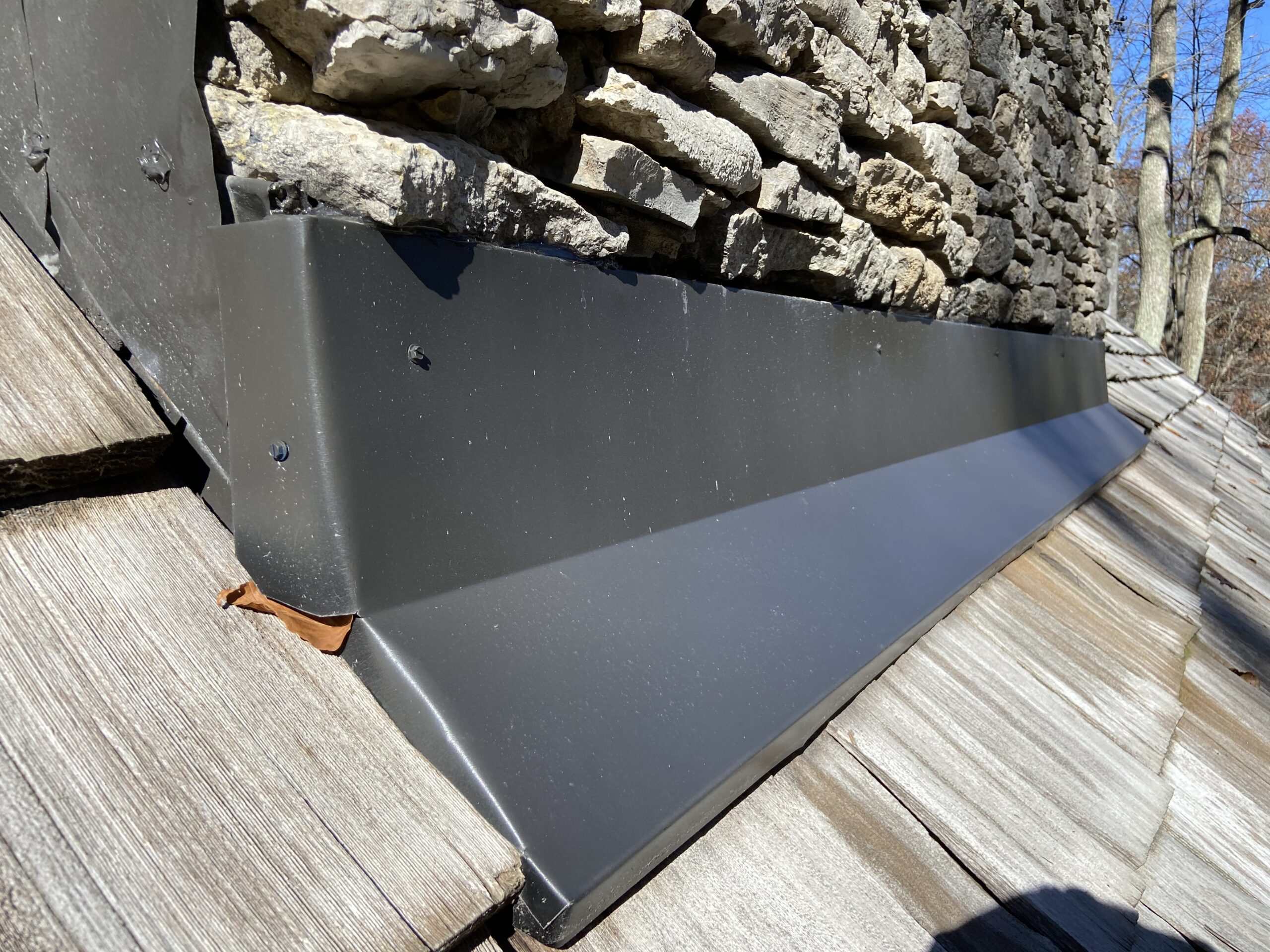 This is a picture of chimney flashing on a wood shake roof