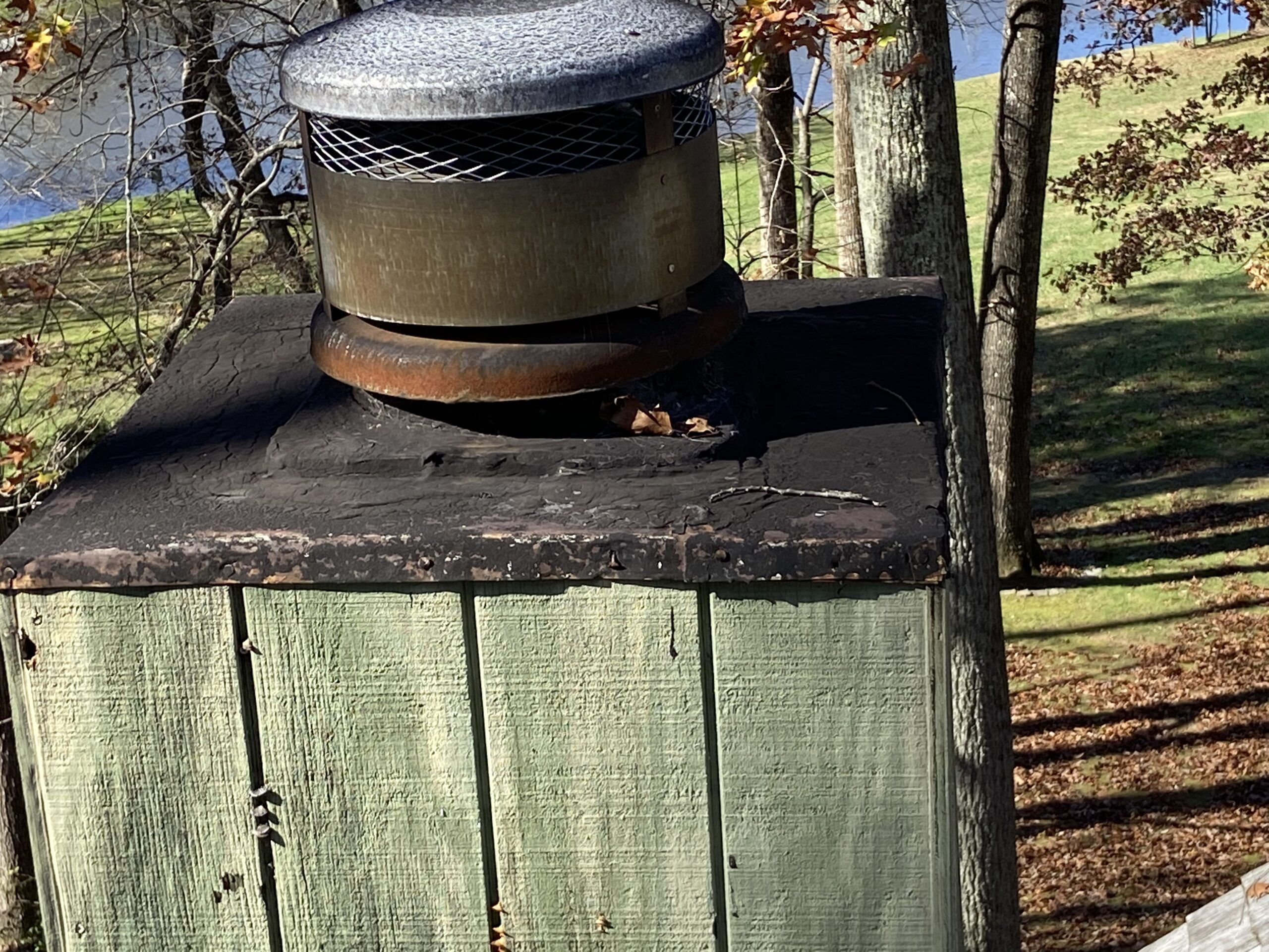 This is a picture of a chimney cap that has some tar on it
